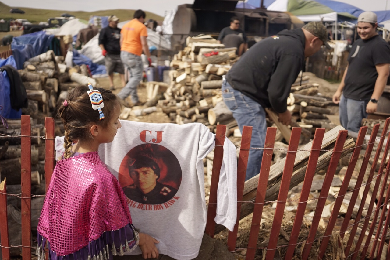 A young Turtle Mountain girl adjusts a shirt honoring her dead brother, C.J. Strong Bear Boy. Her brother died this winter in a car accident on the way to work, after hitting black ice. The Turtle Mountain tribe sent 8 truckloads of firewood here to North Dakota (in CJ's honor) to support the Standing Rock tribe in their growing protest against the construction of an oil pipeline near their reservation. They also sent a half dozen young men to split and stack the wood, which they're giving away to anyone camping at the protest. Photo by William Brangham