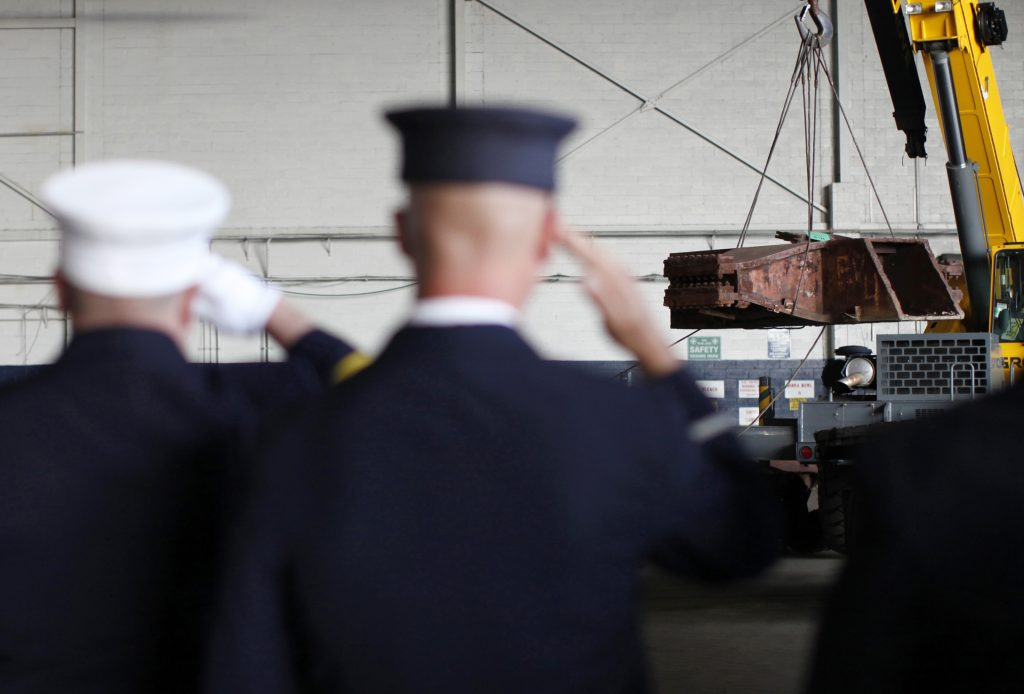Members of the St. James New York Fire Department salute inside Hangar 17 at New York's John F. Kennedy International Airport June 16, 2011, as steel recovered from the 2001 World Trade Center disaster is loaded onto a flatbed truck. A program operated by the Port Authority of New York and New Jersey, The World Trade Center steel program, is selecting portions of the steel recovered from the World Trade Center and donating it to cities, towns, firehouses and museums around the U.S. and the world who request it for use in 911 memorial sites in time for the 10 year anniversary of the 2001 attacks. The flag was laterused to cover a section of steel that the Jamestown Fire Department took for their 911 memorial. Picture taken June 16, 2011. Photo By Mike Segar/Reuters