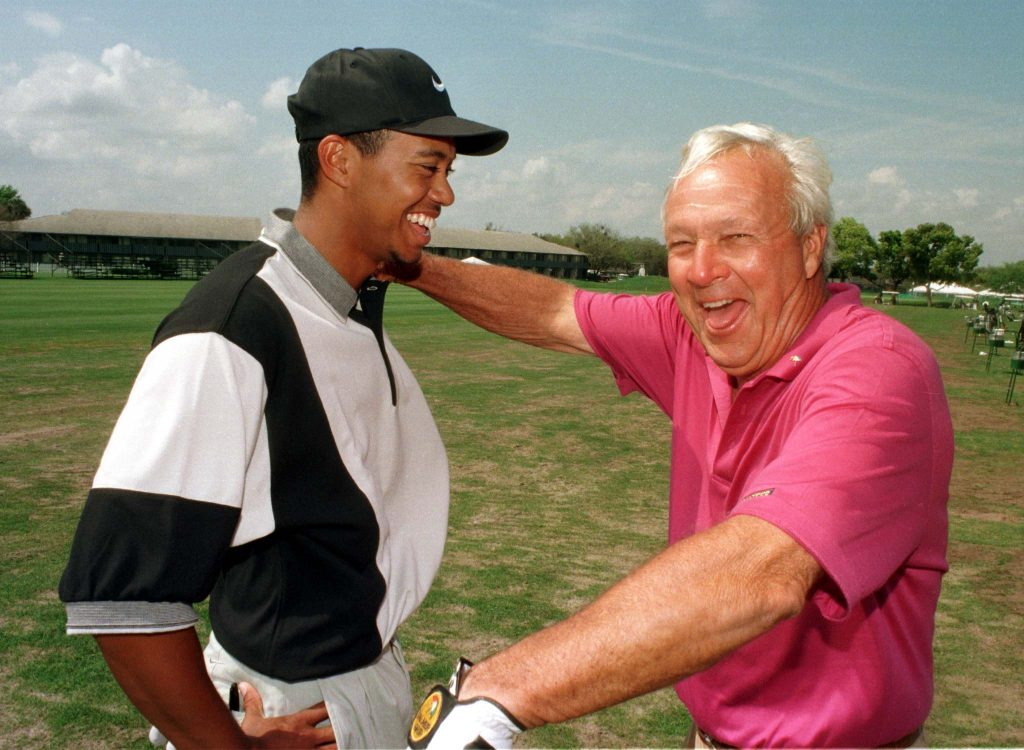 PGA golfers Arnold Palmer (right) and Tiger Woods share a light moment in Ligonier, Pennsylvania, in 1997. Photo by Reuters