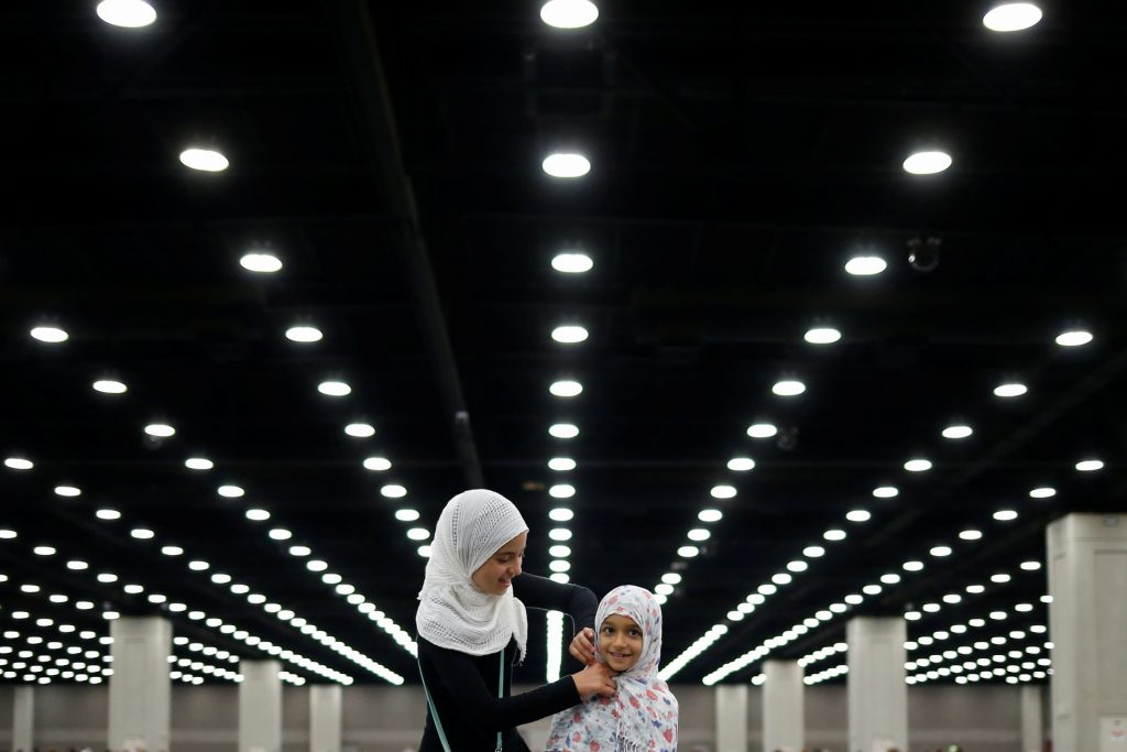 Salma Selenica, 12, (L) adjusts the headscarf of her sister Layla, 8, ahead of the jenazah, an Islamic funeral prayer, for the late boxing champion Muhammad Ali in Louisville, Kentucky, U.S. June 9, 2016.  REUTERS/Adrees Latif TPX IMAGES OF THE DAY - RTSGR2P