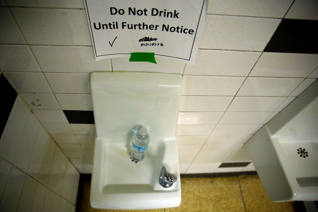 A sign is seen next to a water dispenser at North Western high school in Flint, a city struggling with the effects of lead-poisoned drinking water, in Michigan May 4, 2016. REUTERS/Carlos Barria - RTX2CVJ1