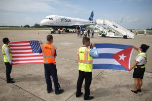 Ground crew hold U.S. and Cuban flags near a recently landed JetBlue aeroplane, the first commercial scheduled flight between the United States and Cuba in more than 50 years, at the Abel Santamaria International Airport in Santa Clara, Cuba, August 31, 2016. Photo by Alexandre Meneghini/REUTERS