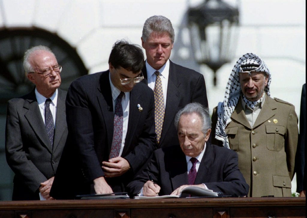 Israeli Foreign Minister Shimon Peres signs the peace accord between Israel and the PLO Sept. 13, 1993, while (left to right) Israeli Prime Minister Yitzhak Rabin, U.S. presidential aide John Podesta, U.S. President Bill Clinton and PLO Chairman Yasser Arafat look on. Photo by Gary Hershorn/Reuters