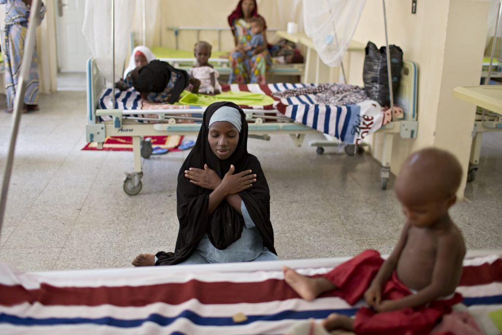 Fatima Ibrahim, center, prays near the bedside of her 2-year-old child Ibrahim, who is being treated for severe malnutrition at an IRC clinic in Maiduguri. Photo by Danielle Villasana