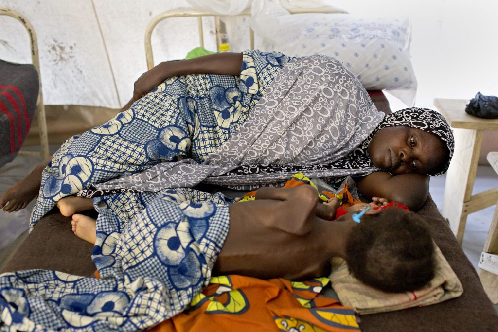 Hadiza Mohammad, 40, lies with her 4-year-old child who's being treated for severe malnutrition at an MSF clinic in Maiduguri. Hadiza fled from her village of Gowza due to Boko Haram violence. Photo by Danielle Villasana