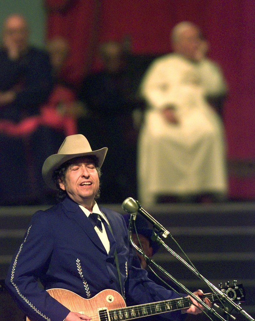 Bob Dylan performs in front of Pope John Paul II during an open air concert in Bologna, Italy, on Sept. 27, 1997. Photo by Paolo Cocco/Reuters