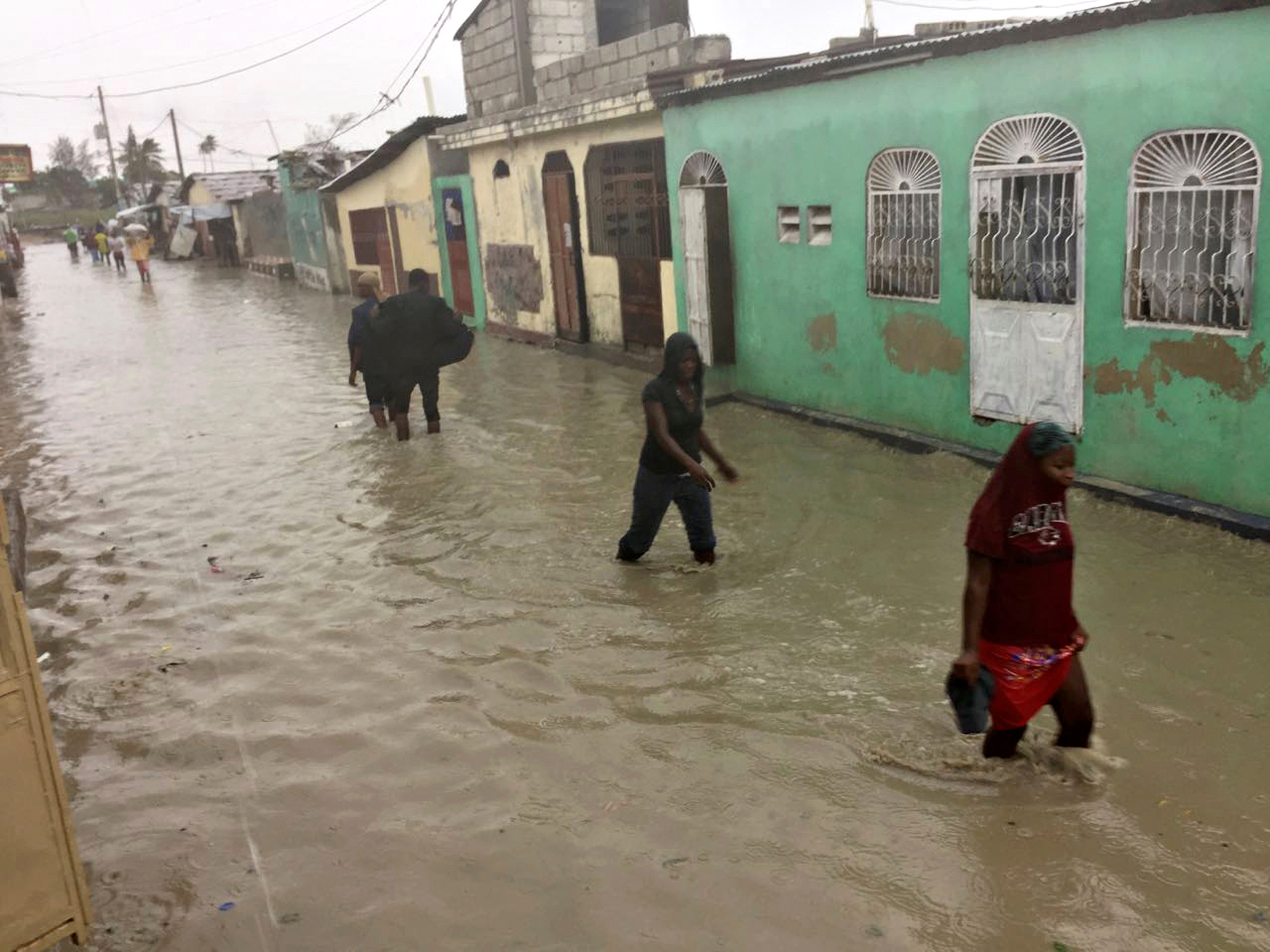 People wade through a flooded street in the impoverished Cite-Soleil neighborhood of Port-au-Prince. Photo by Carlos Garcia Rawlins/Reuters
