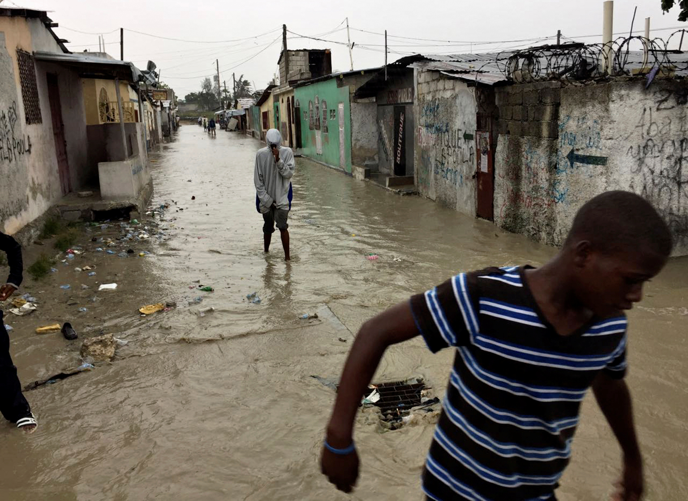 Murky water rushed through the Cite-Soleil commune on Oct. 4. Water-spread diseases are now a concern following Hurricane Matthew. Photo by Carlos Garcia Rawlins/Reuters