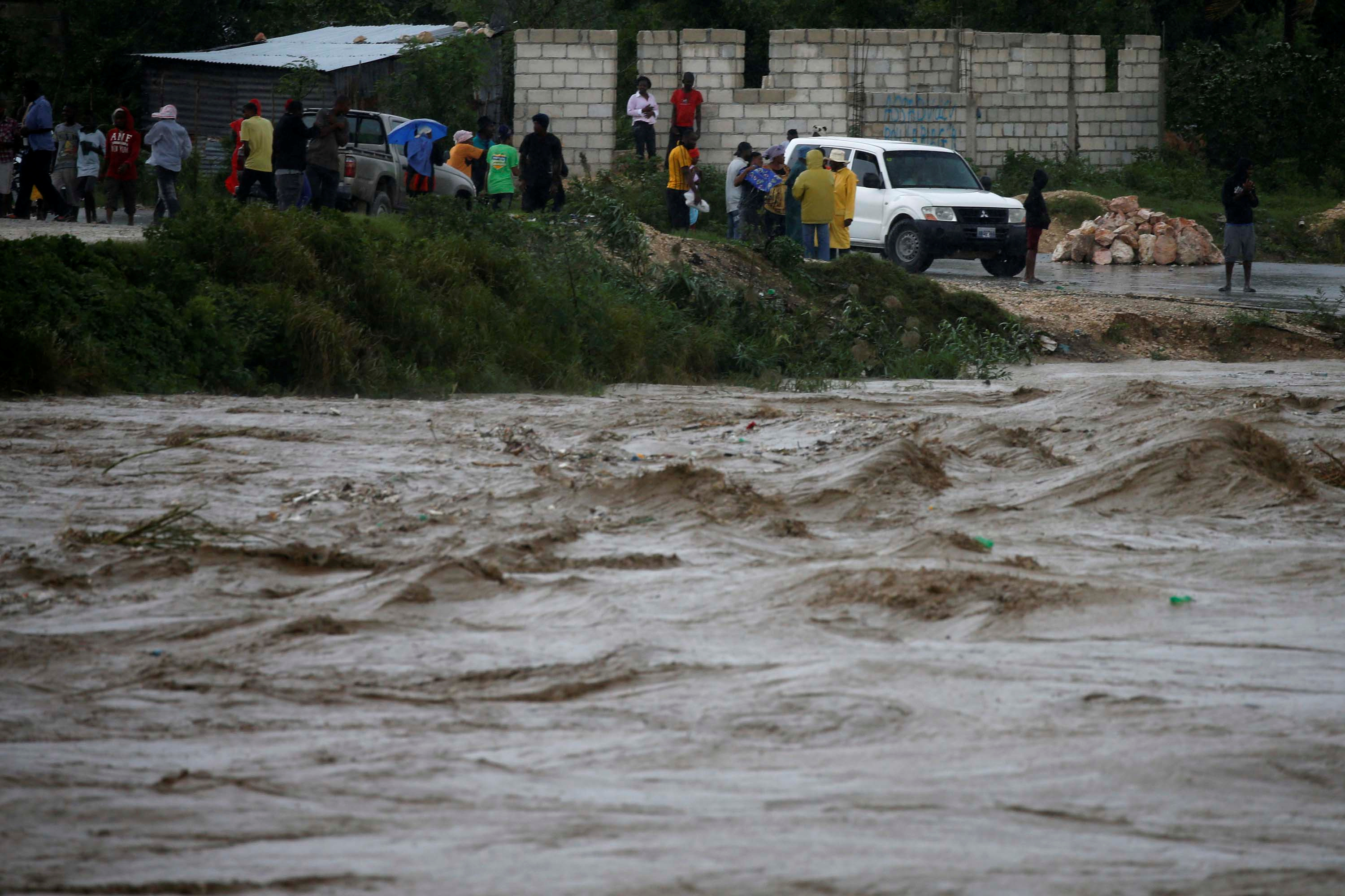 People watch as river waters roll through Port-au-Prince on Oct. 4. Photo by Carlos Garcia Rawlins/Reuters