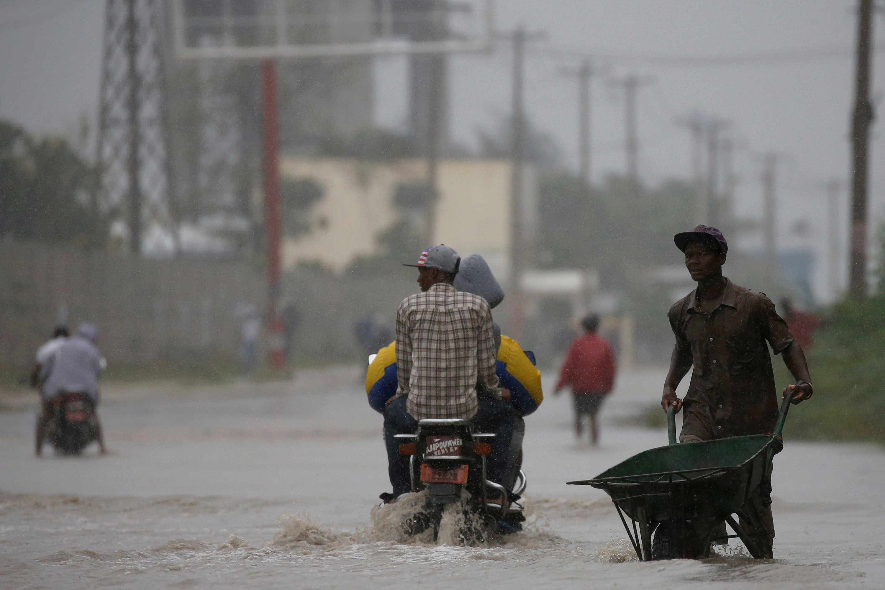 A man wades across a flooded street in Port-au-Prince. Photo by Carlos Garcia Rawlins/Reuters