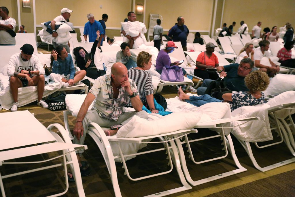 People listen to an update on Hurricane Matthew after speding a night on beach chairs in a ballroom at the Melia Hotel in Nassau, Bahamas October 6, 2016. REUTERS/Carlo Allegri
