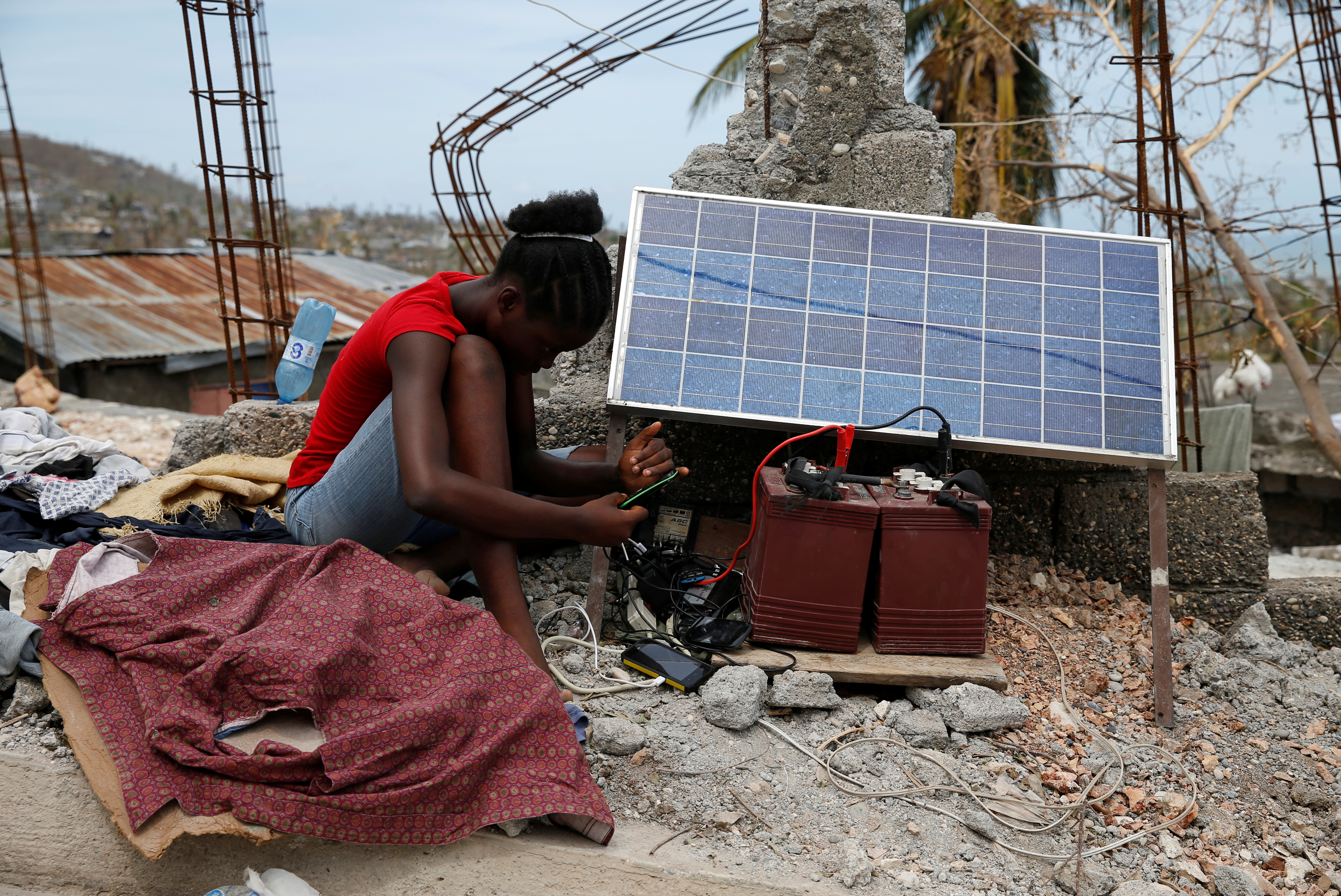 A woman uses solar panels to recharge her mobile phone in Jeremie, Haiti. Photo by Carlos Garcia Rawlins/Reuters