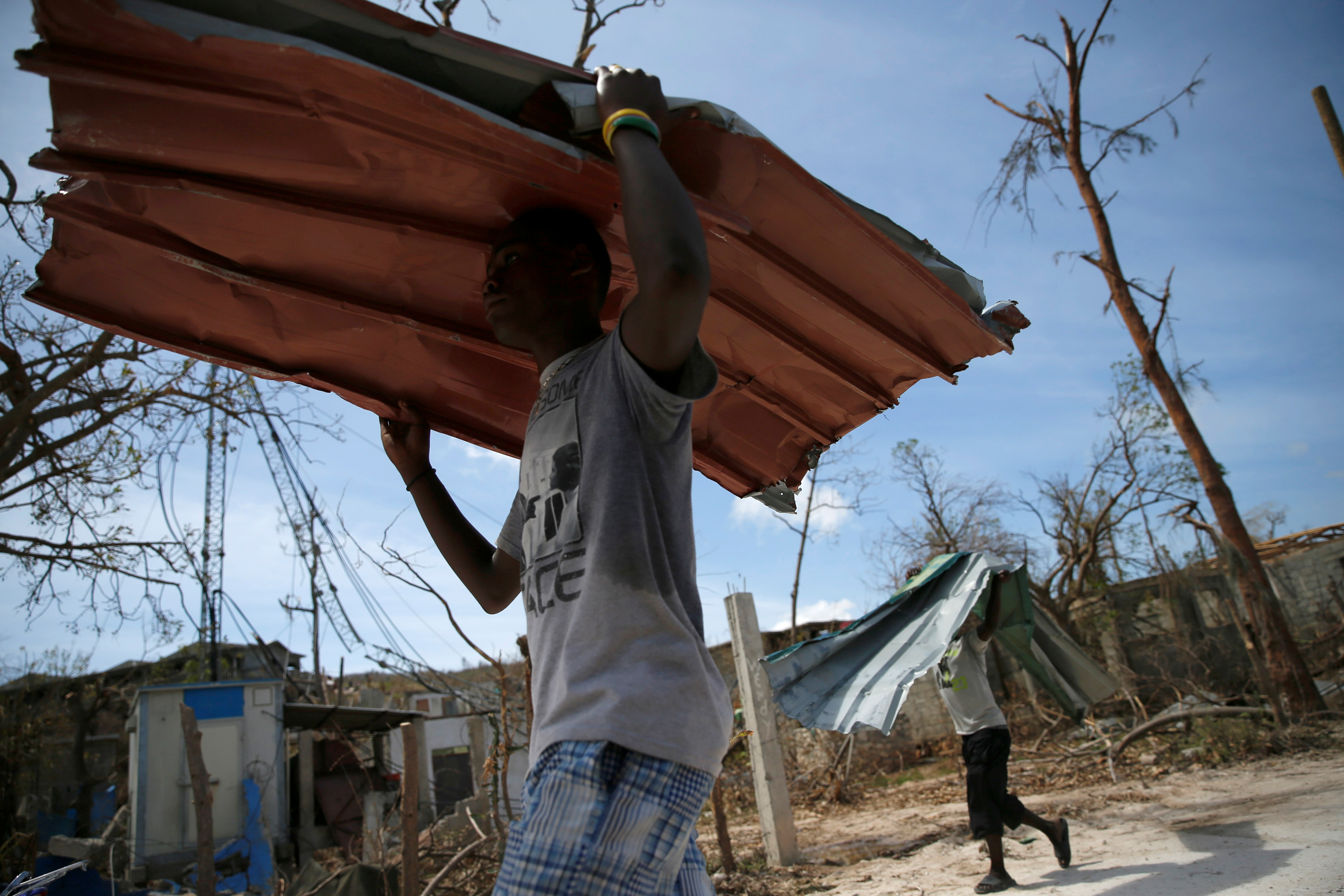 Men carry metal sheets to help rebuild homes in the commune of Jeremie, Haiti. Photo by Carlos Garcia Rawlins/Reuters