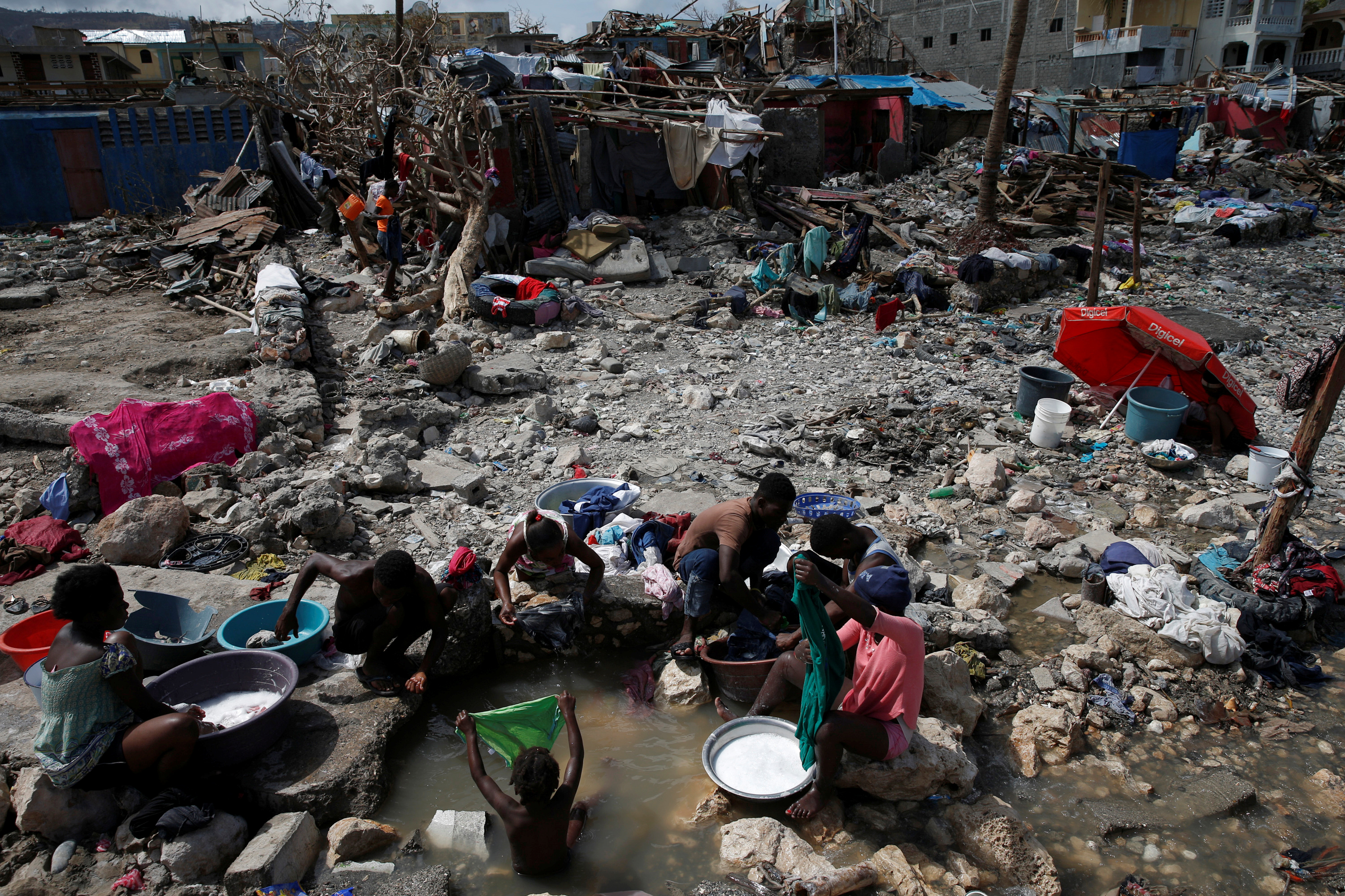 People wash their clothes on a beach near destroyed houses. Photo by Carlos Garcia Rawlins/Reuters