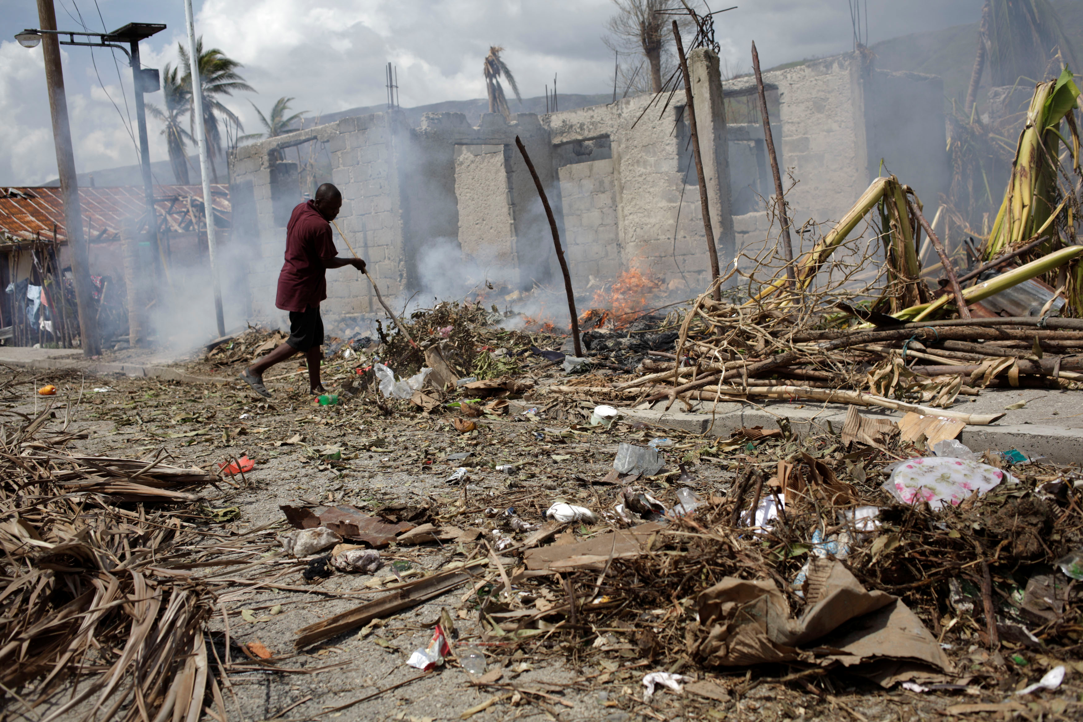 A man burns branches from fallen trees in Les Anglais in southwestern Haiti. Photo by Andres Martinez Casares/Reuters