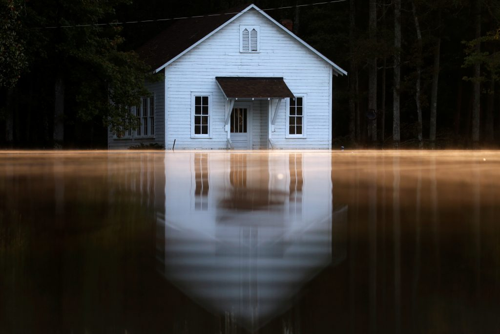 Mist rises off the water as a flooded building is pictured after Hurricane Matthew passes in Lumberton, North Carolina. Photo by Carlo Allegri/Reuters
