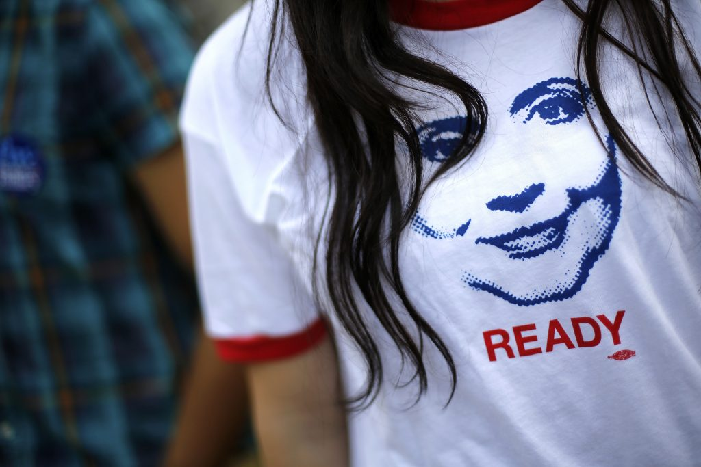 "A supporter of former U.S. Secretary of State Hillary Clinton wears a T-shirt with an image depicting her as people arrive to hear her speak about her new book ""Hard Choices"" at the George Washington University in Washington June 13, 2014. REUTERS/Jonathan Ernst/File Photo - RTX2PSB5"