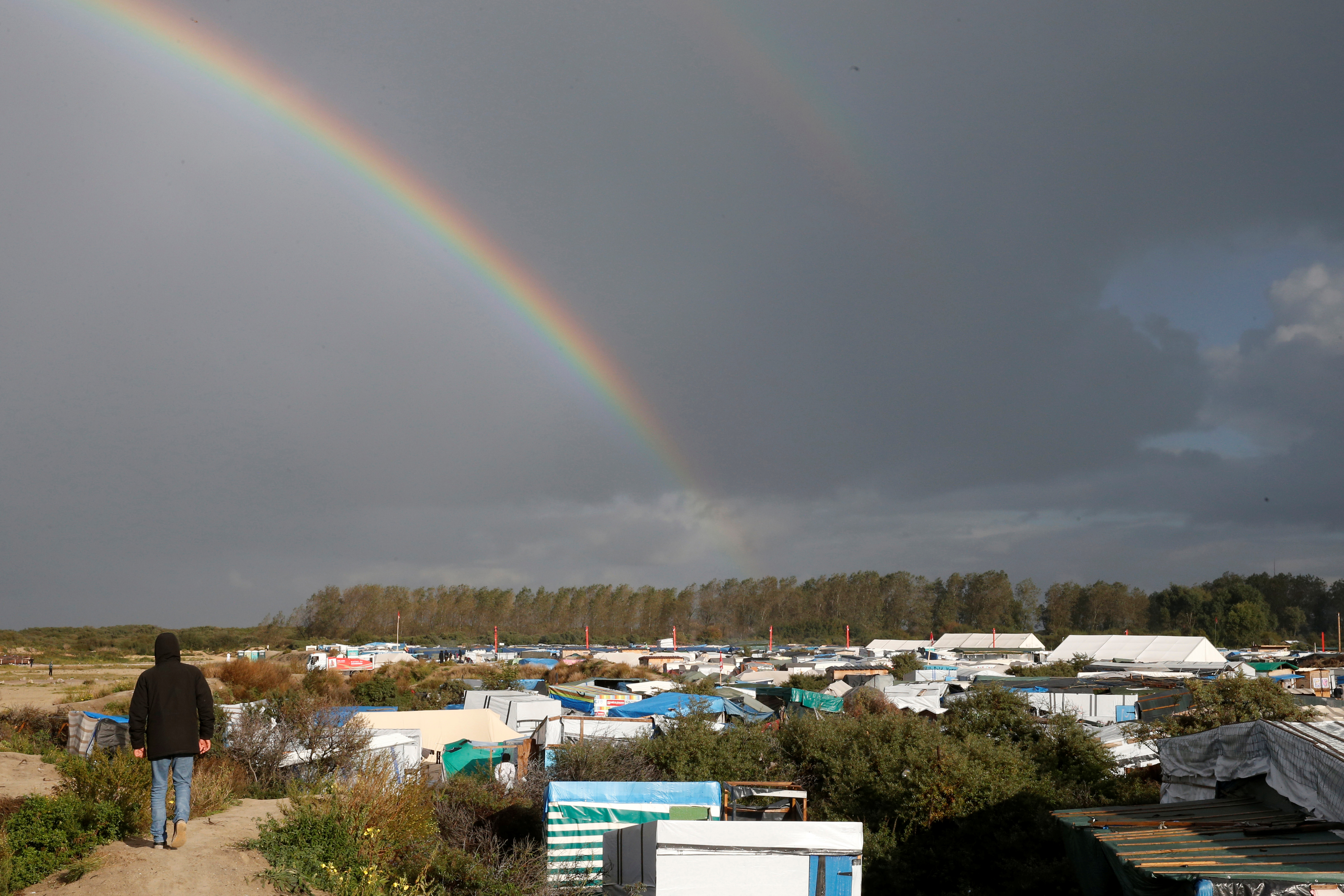 "An migrant walks on a ridge towards a double rainbow that appears over the makeshift camp called the ""Jungle"" in Calais, France, October 22, 2016. REUTERS/Pascal Rossignol  - RTX2PZRF"