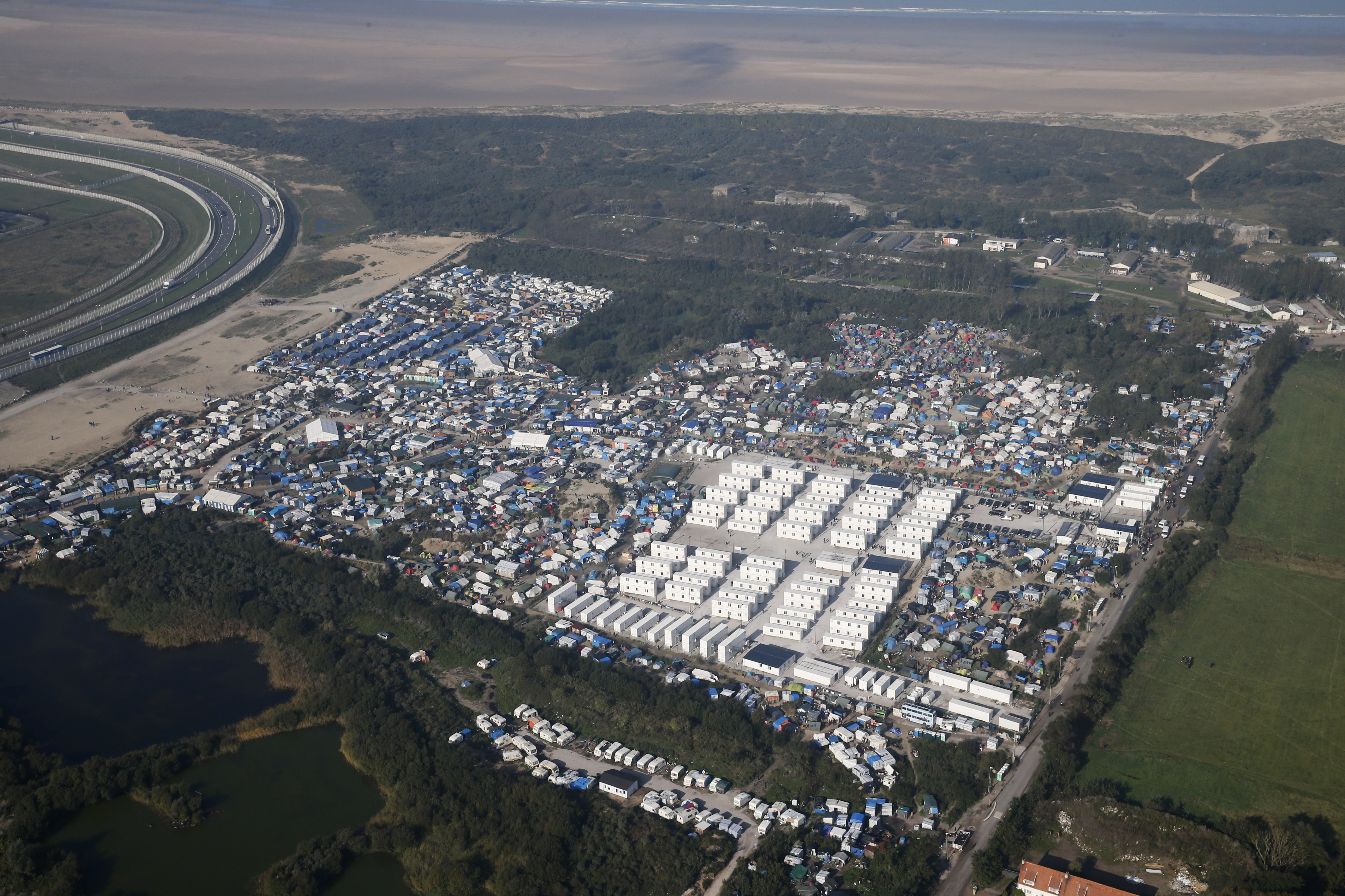 "An aerial view shows white containters, tents and makeshift shelters on the eve of the evacuation and dismantlement of the camp called the ""Jungle"" in Calais, France, October 23, 2016.    REUTERS/Pascal Rossignol  TPX IMAGES OF THE DAY - RTX2Q2BW"