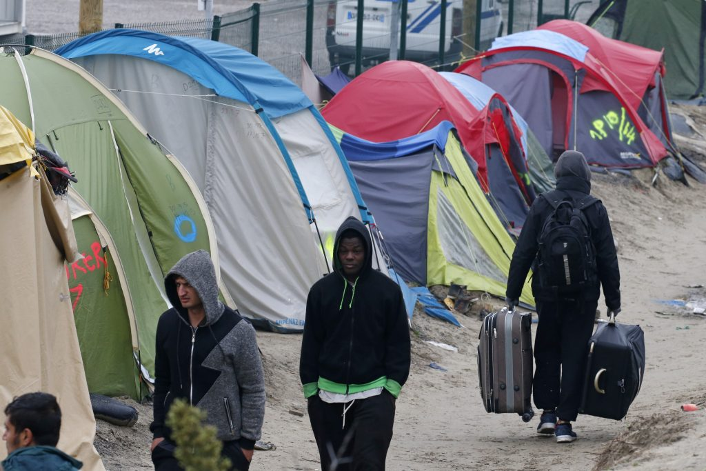"Migrants with their belongings walk past tents at the start of their evacuation and transfer to reception centers in France, and the dismantlement of the camp called the ""Jungle"" in Calais, France, October 24, 2016. Photo by Pascal Rossignol/REUTERS"