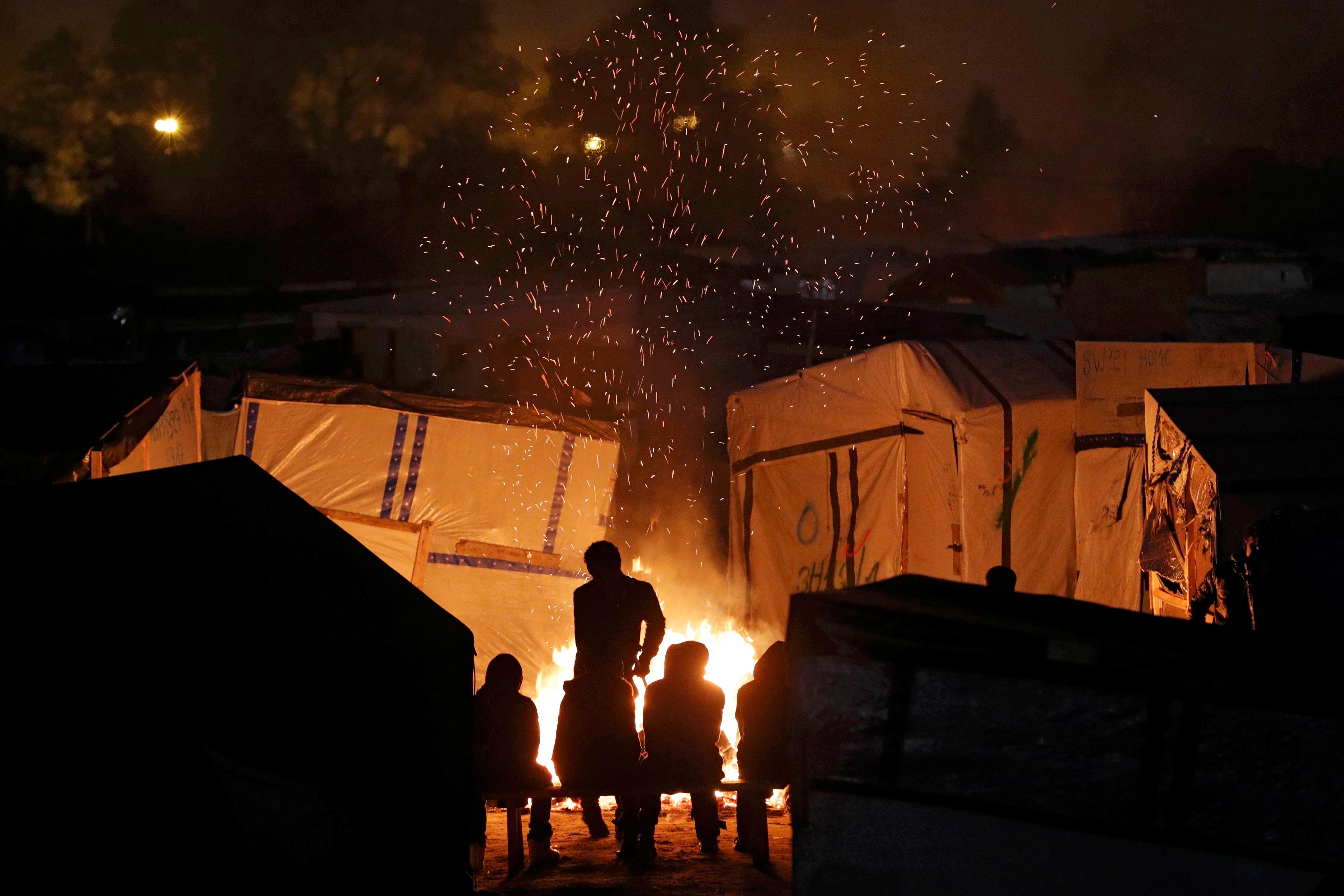 "Sparks fly from a fire as migrants sit near for warmth at the end of the first day of the evacuation and transfer to reception centers of migrants living in the ""Jungle"" in Calais, France, October 24, 2016.  REUTERS/Philippe Wojazer       TPX IMAGES OF THE DAY      - RTX2Q9XZ"