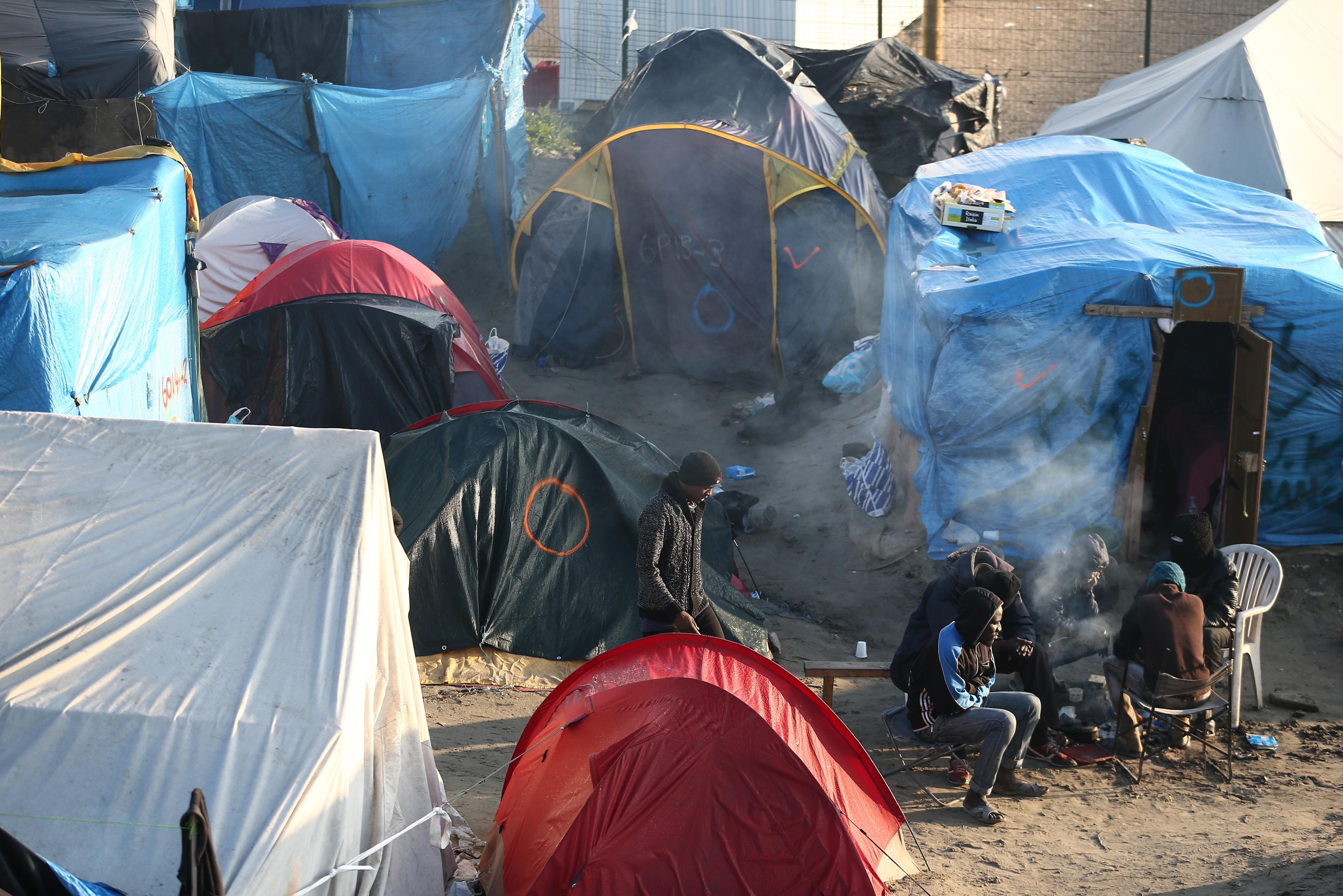 "Migrants stand next to tents and makeshift shelters on the second day of their evacuation and transfer to reception centers in France, during the dismantlement of the camp called the ""Jungle"" in Calais, France, October 25, 2016.    REUTERS/Neil Hall  - RTX2QBQJ"
