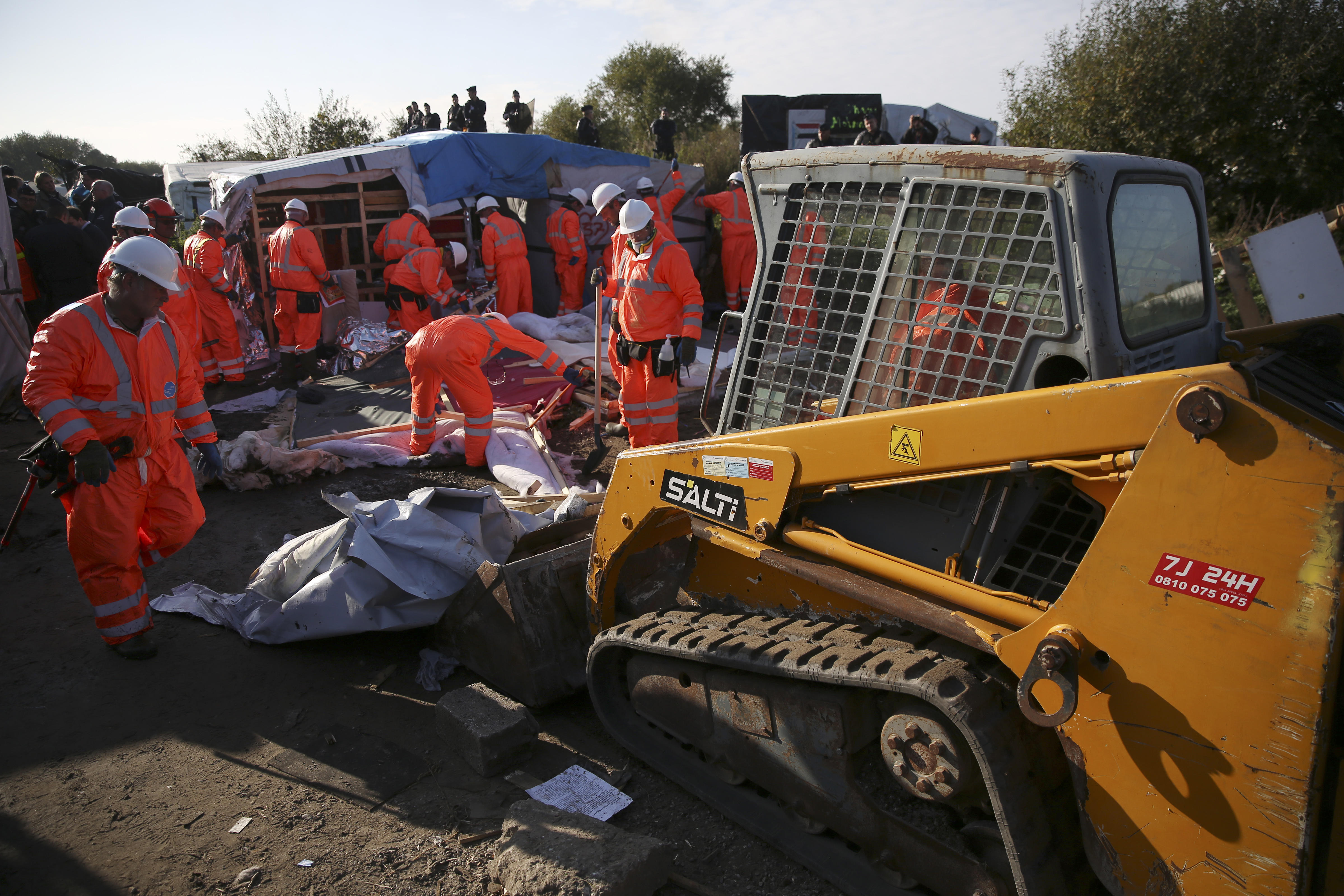 "Workmen remove debris as they tear down makeshift shelters on the second day the evacuation of migrants and their transfer to reception centers in France, as part of the dismantlement of the camp called the ""Jungle"" in Calais, France, October 25, 2016.      REUTERS/Neil Hall   - RTX2QD3H"