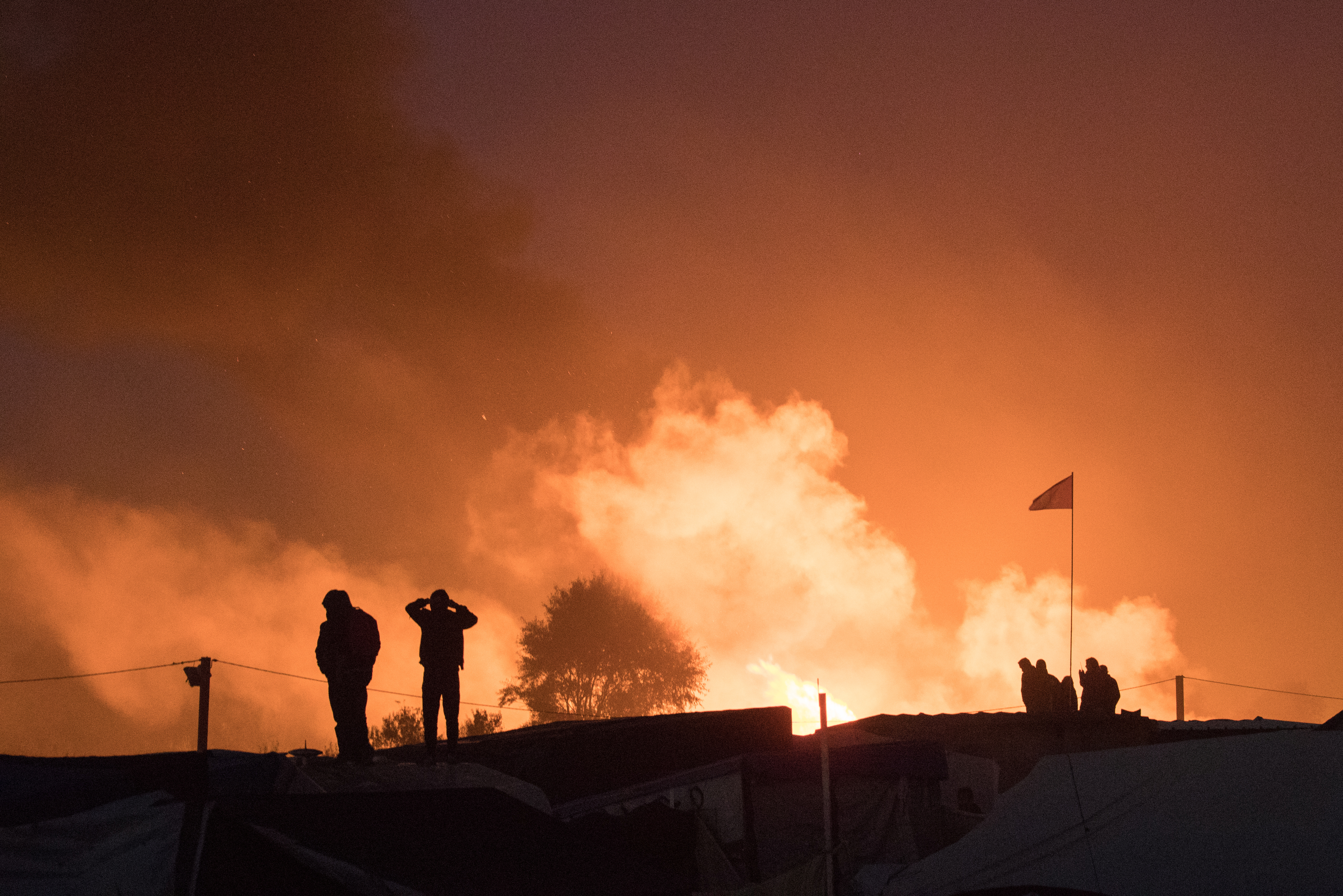 "Migrants are seen in silhouette as they gather near flames from a burning makeshift shelter on the second day of the evacuation of migrants and their transfer to reception centers in France, as part of the dismantlement of the camp called the ""Jungle"" in Calais, France, October 25, 2016. REUTERS/Philippe Wojazer"