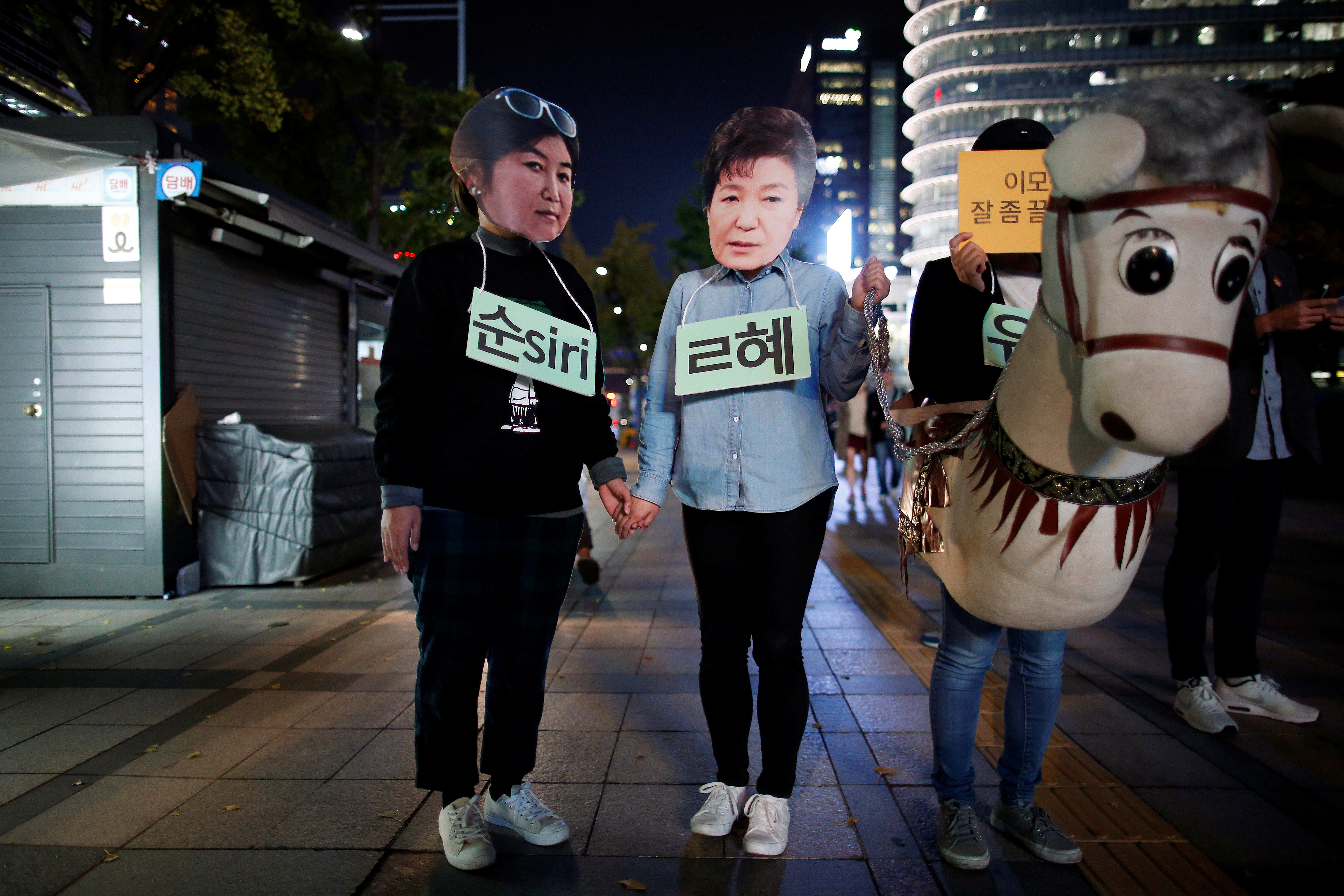 Protesters wearing cut-out of South Korean President Park Geun-hye (C) and Choi Soon-sil attend a protest denouncing President Park Geun-hye over a recent influence-peddling scandal in central Seoul, South Korea, October 27, 2016. REUTERS/Kim Hong-Ji - RTX2QP5W