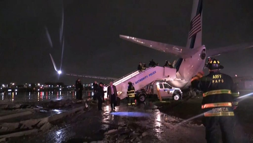 Emergency workers stand in front of the plane carrying U.S. Republican vice presidential nominee Mike Pence after it skidded off the runway after landing in the rain at New York City's LaGuardia Airport on Thursday, in this still image taken from video October 27, 2016. COURTESY US TV POOL/via Reuters