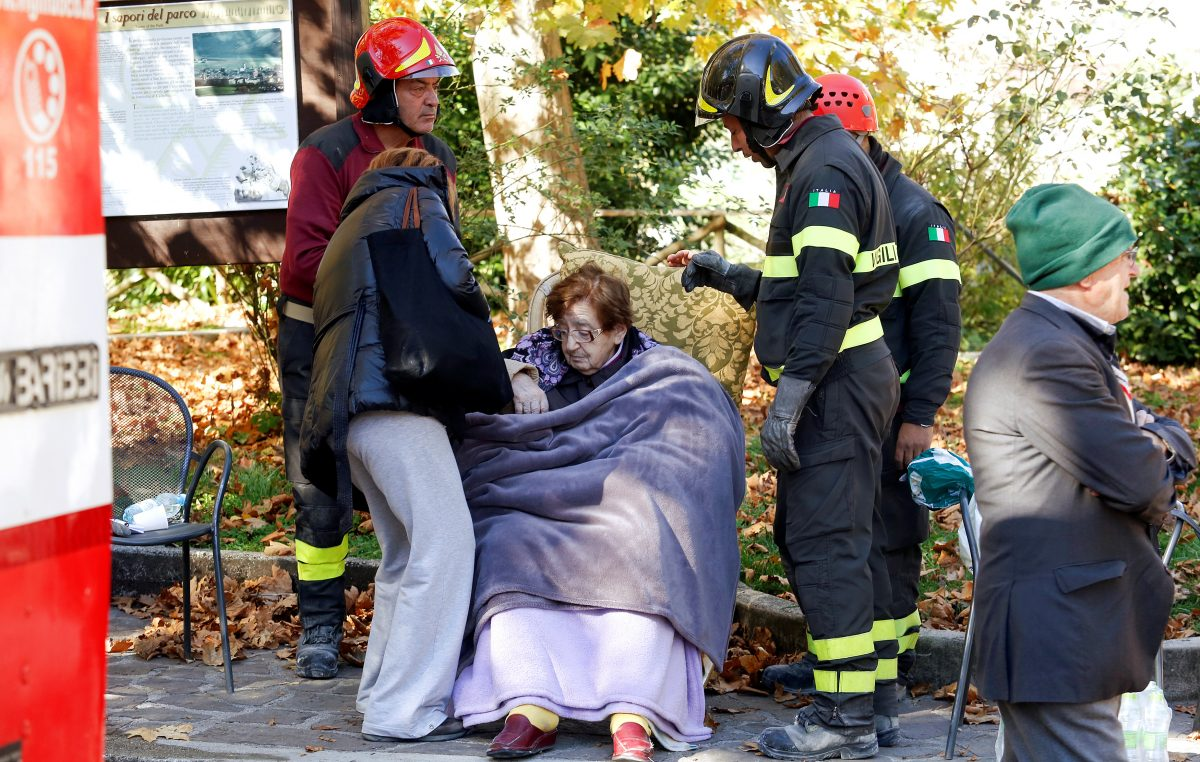 Firefighters take care of a woman following an earthquake in Norcia, Italy, October 30, 2016. Photo By Remo Casilli/Reuters