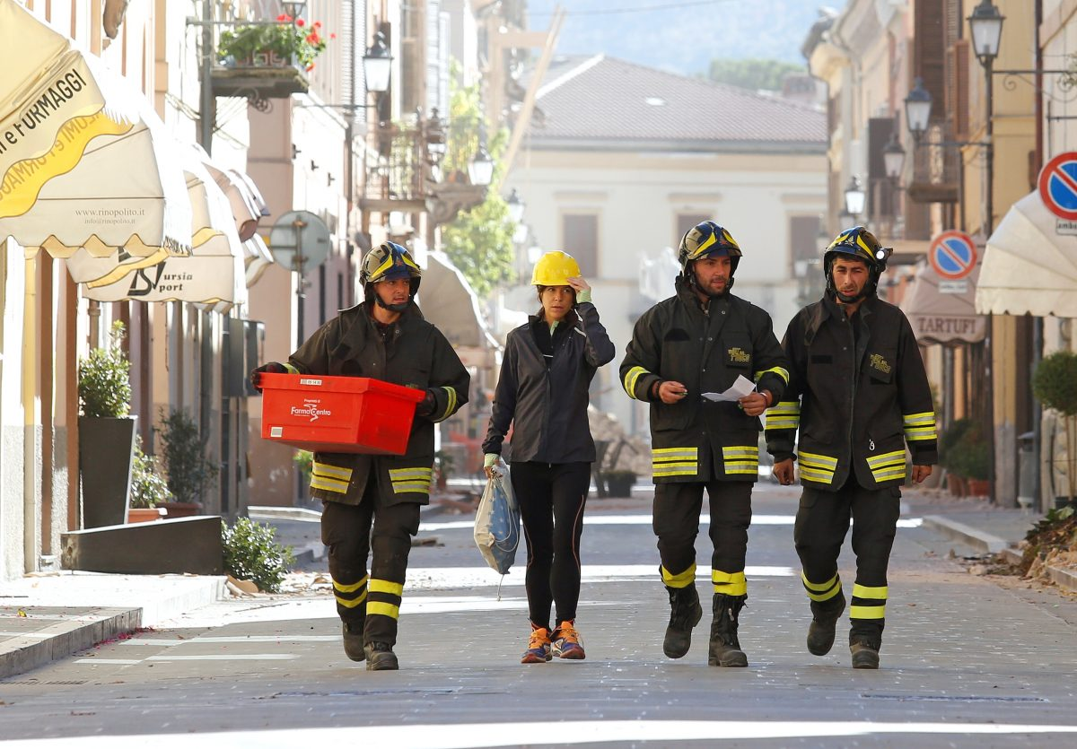 Firefighters carry belongings of a resident following an earthquake in Norcia, Italy, October 30, 2016. Photo By Remo Casilli/Reuters