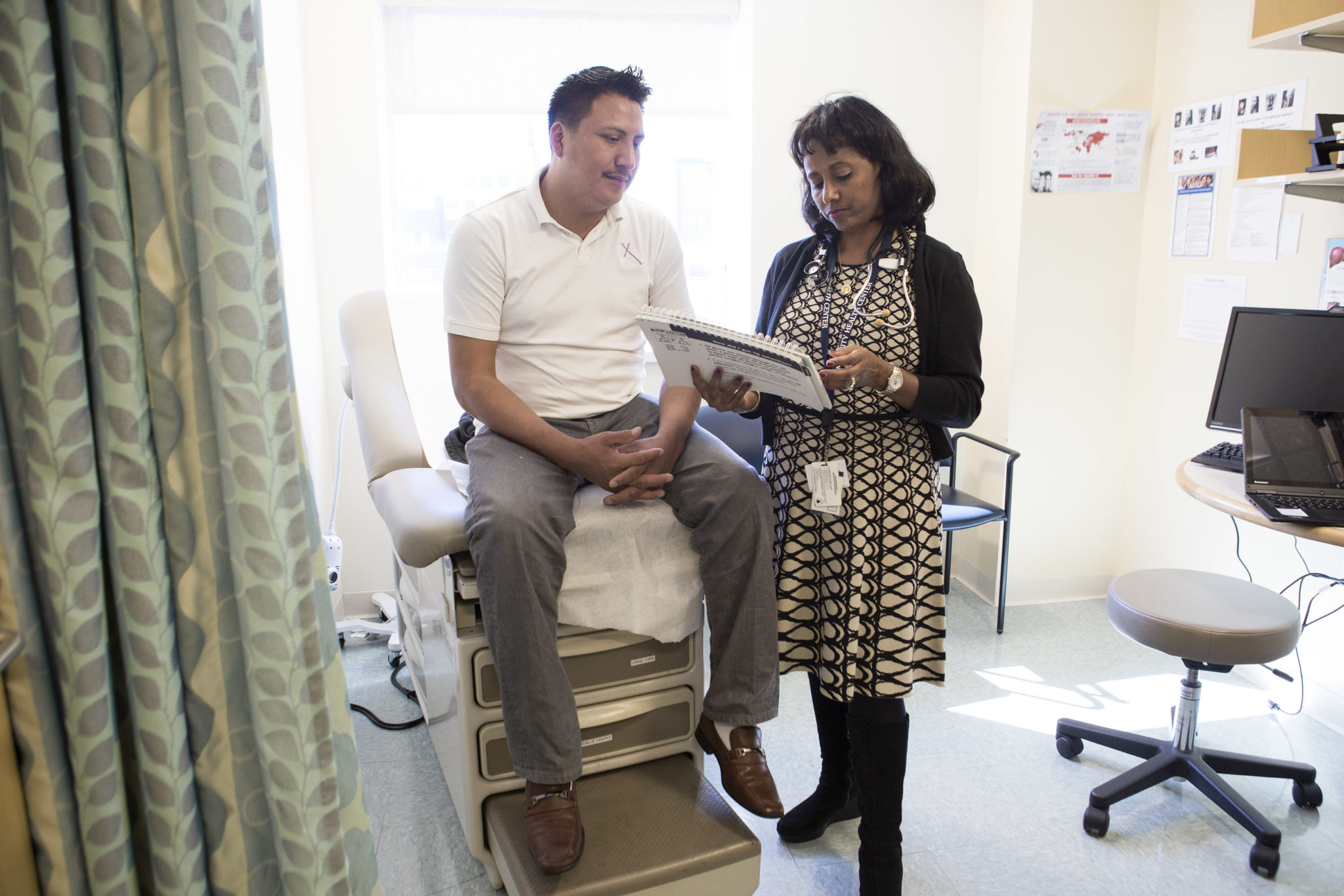 Dr. Hanna Haptu, right, discussing TB infection with a patient who was diagnosed with latent tuberculosis two months ago. He visits the clinic in Lynn monthly. Photo by Kayana Szymczak for STAT