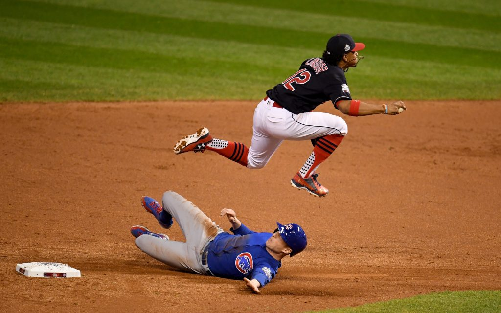 Francisco Lindor (12) of the Cleveland Indians jumps over Chris Coghlan (8) of the Chicago Cubs as Coghlan is out at second base in the 9th inning in Game 7 of the 2016 World Series at Progressive Field in Cleveland, Ohio. Photo by Jason Miller/Getty Images