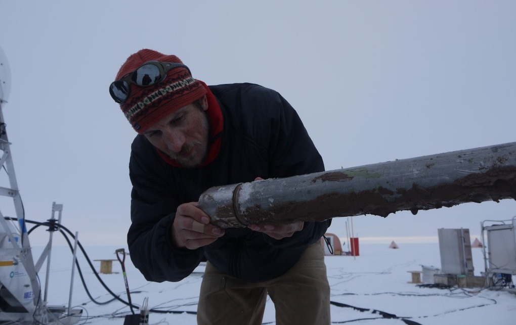 Marine Geologist James Smith inspects sediment core recovered from beneath a more than 1,000 foot thick portion of the Pine Island Glacier ice shelf. Photo courtesy M. Brian/Nature