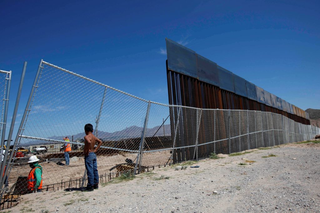 A boy looks as U.S. workers build a section of the U.S.-Mexico border wall at Sunland Park, U.S. opposite the Mexican border city of Ciudad Juarez, Mexico. Photo by Jose Luis Gonzalez/Reuters