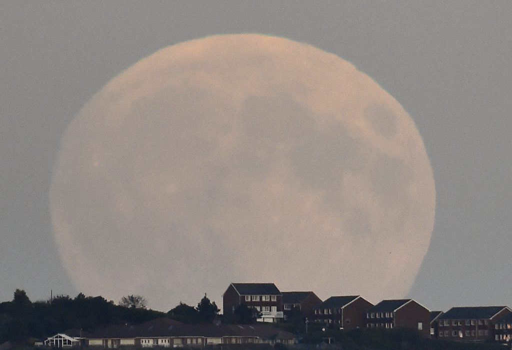 "A ""supermoon'' rises above Brighton in southern England September 27, 2015. Sky-watchers around the world are in for a treat Sunday night and Monday when the shadow of Earth casts a reddish glow on the moon, the result of rare combination of an eclipse with the closest full moon of the year. The total ""supermoon"" lunar eclipse, also known as a ""blood moon"" is one that appears bigger and brighter than usual as it reaches the point in its orbit that is closest to Earth. Photo by Toby Melville/REUTERS"