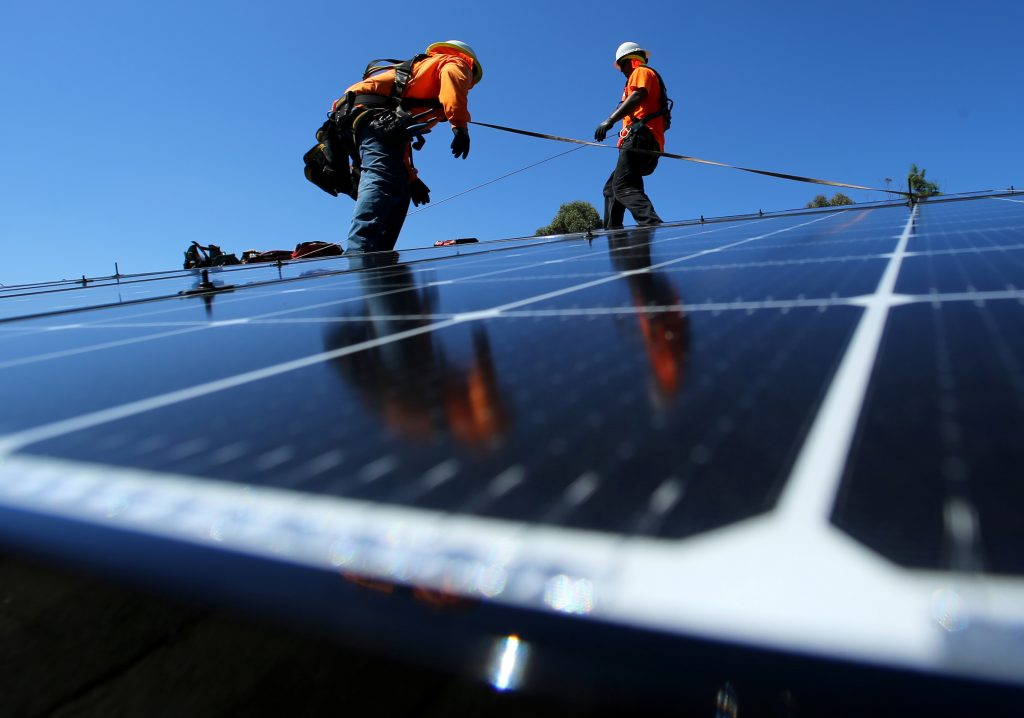 Solar installers from Baker Electric place solar panels on the roof of a residential home in Scripps Ranch, San Diego, California, U.S. October 14, 2016. Photo by Mike Blake/REUTERS