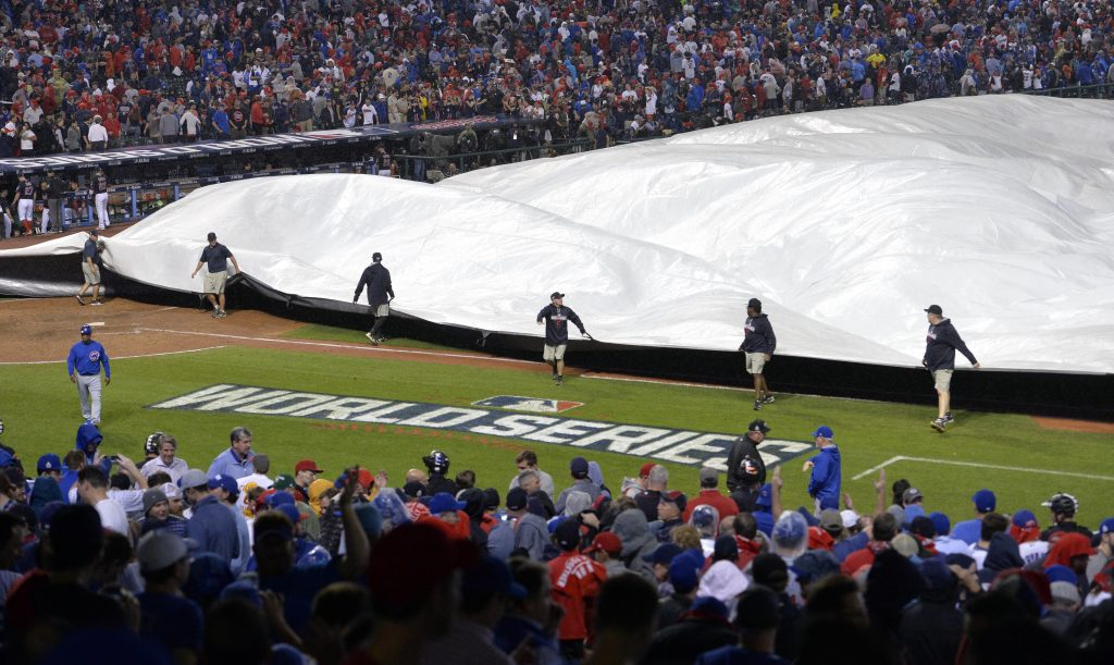 Grounds crew members pull the tarp on the field in the 10th inning in game seven of the 2016 World Series between the Chicago Cubs and the Cleveland Indians at Progressive Field. Photo by David Richard/USA TODAY Sports