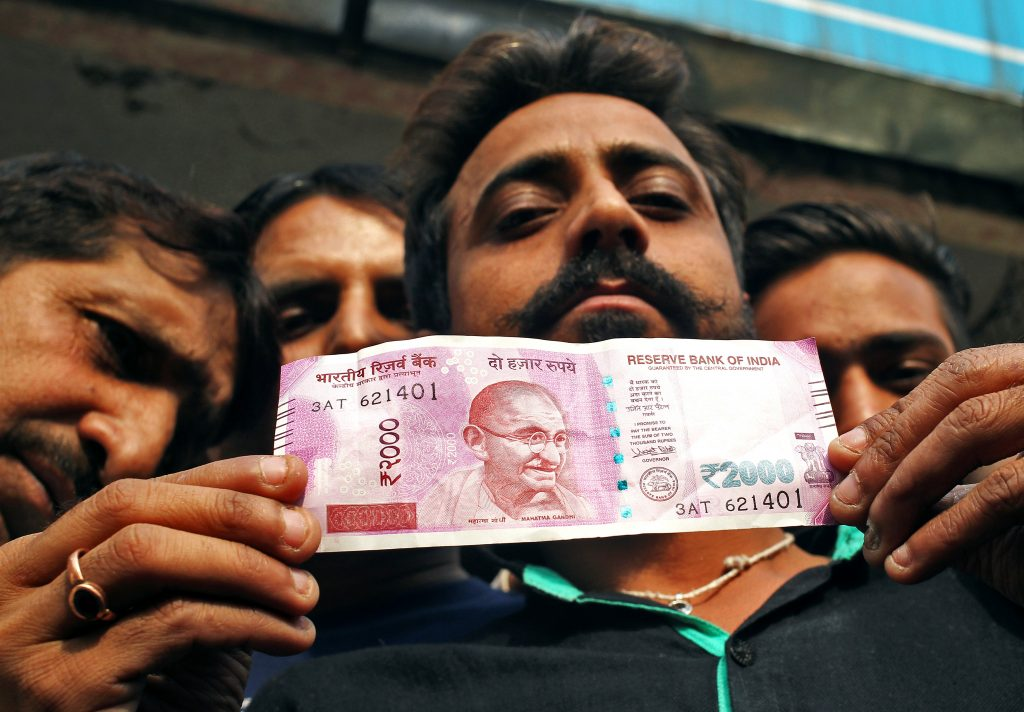 A man displays a new 2000 Indian rupee banknote after withdrawing from a bank in Jammu, November 11, 2016. Photo By Mukesh Gupta/Reuters