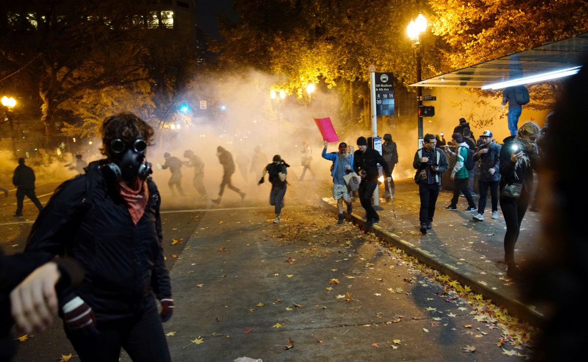 People try to move away from a gas cloud during a protest against the election of Republican Donald Trump as President of the United States in Portland, Oregon, U.S. November 12, 2016. REUTERS/William Gagan FOR EDITORIAL USE ONLY. NO RESALES. NO ARCHIVES - RTX2TBD3