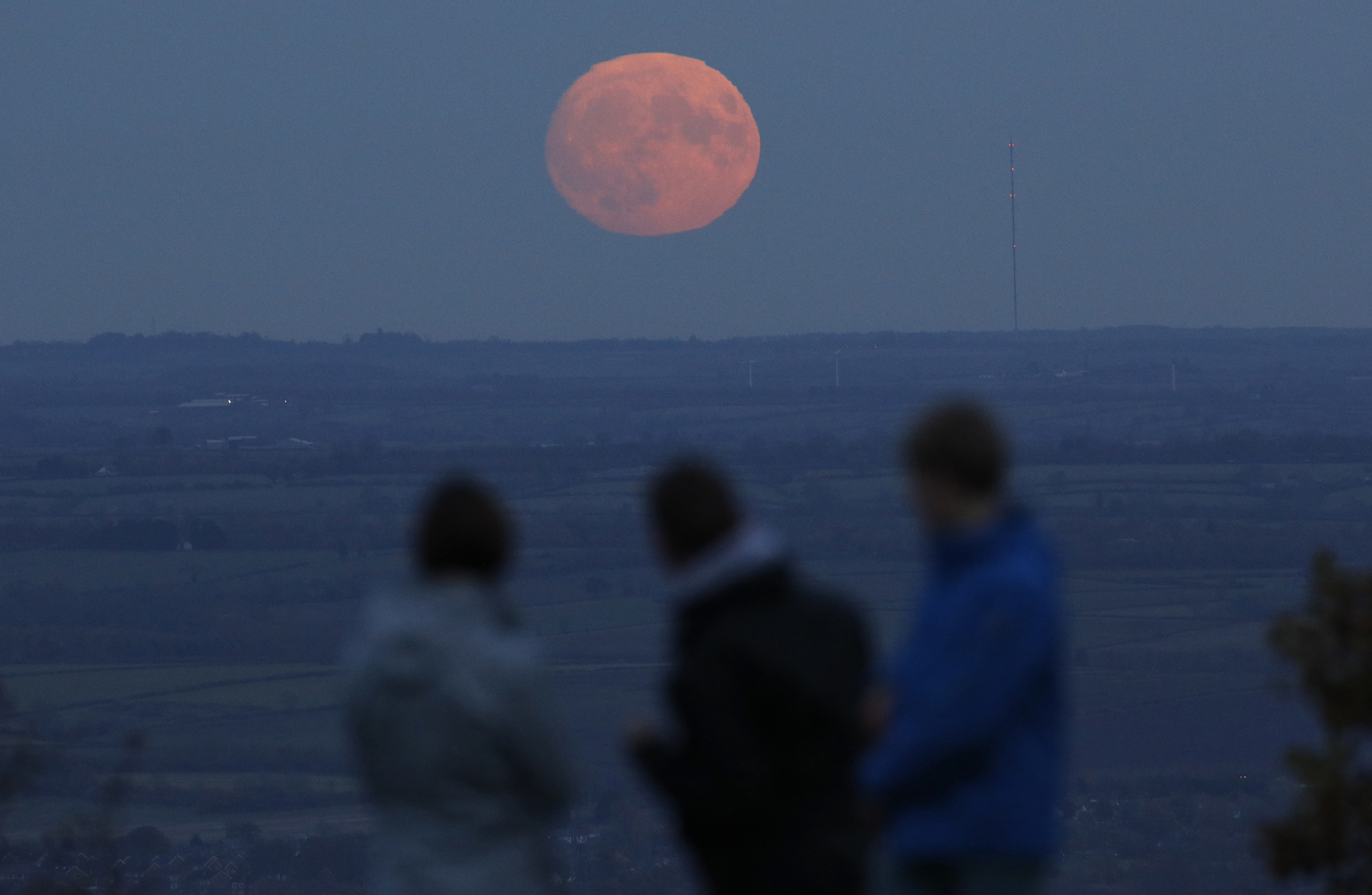 "A family watches the moon rise a day before the ""supermoon"" viewing on Beacon Hill near Loughborough, Britain. Photo by Darren Staples/Reuters"