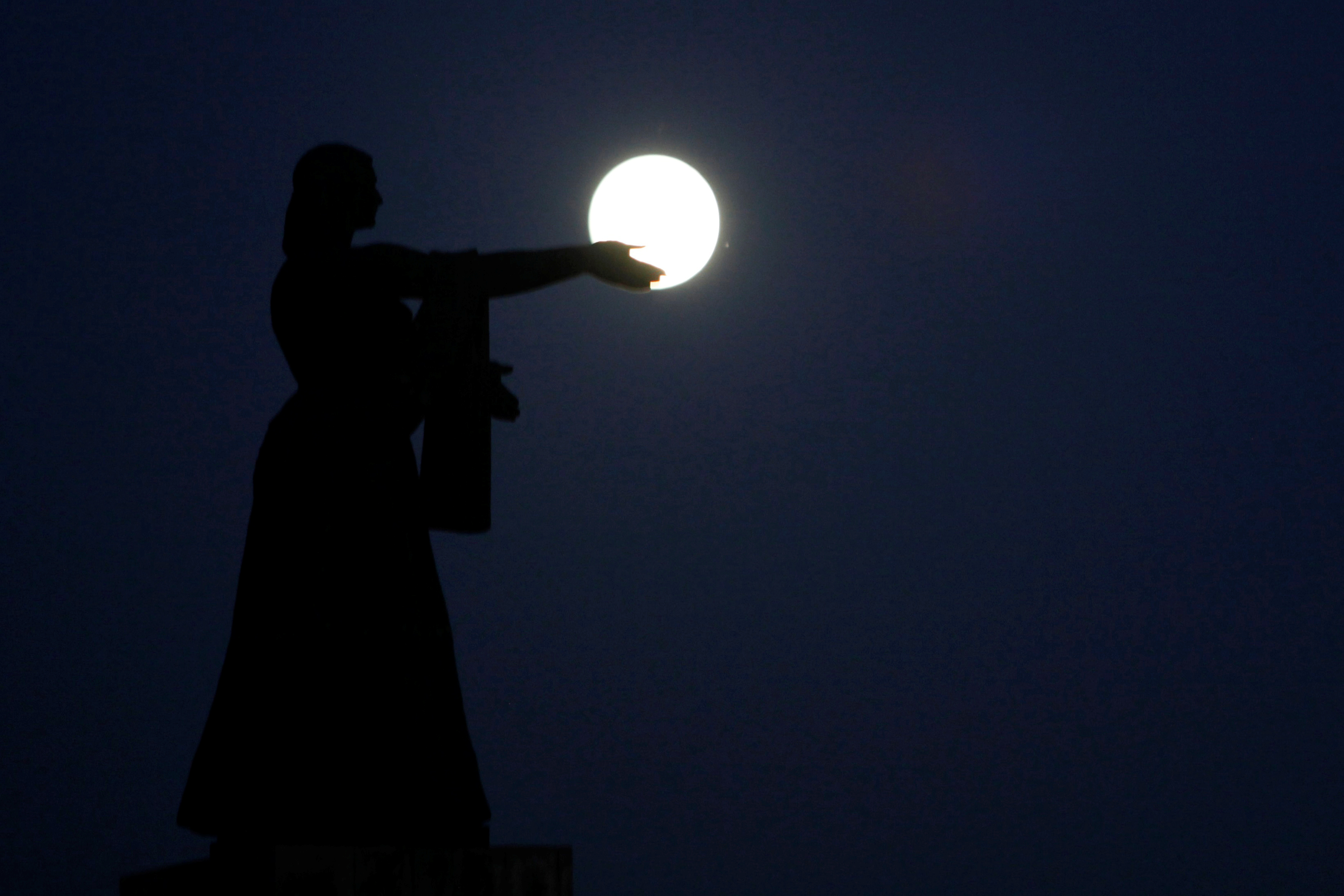 The supermoon, the closest the full moon has come to Earth since 1948, rises over La Raza monument in Ciudad Juarez, Mexico on Nov. 13. Photo by Jose Luis Gonzalez/Reuters