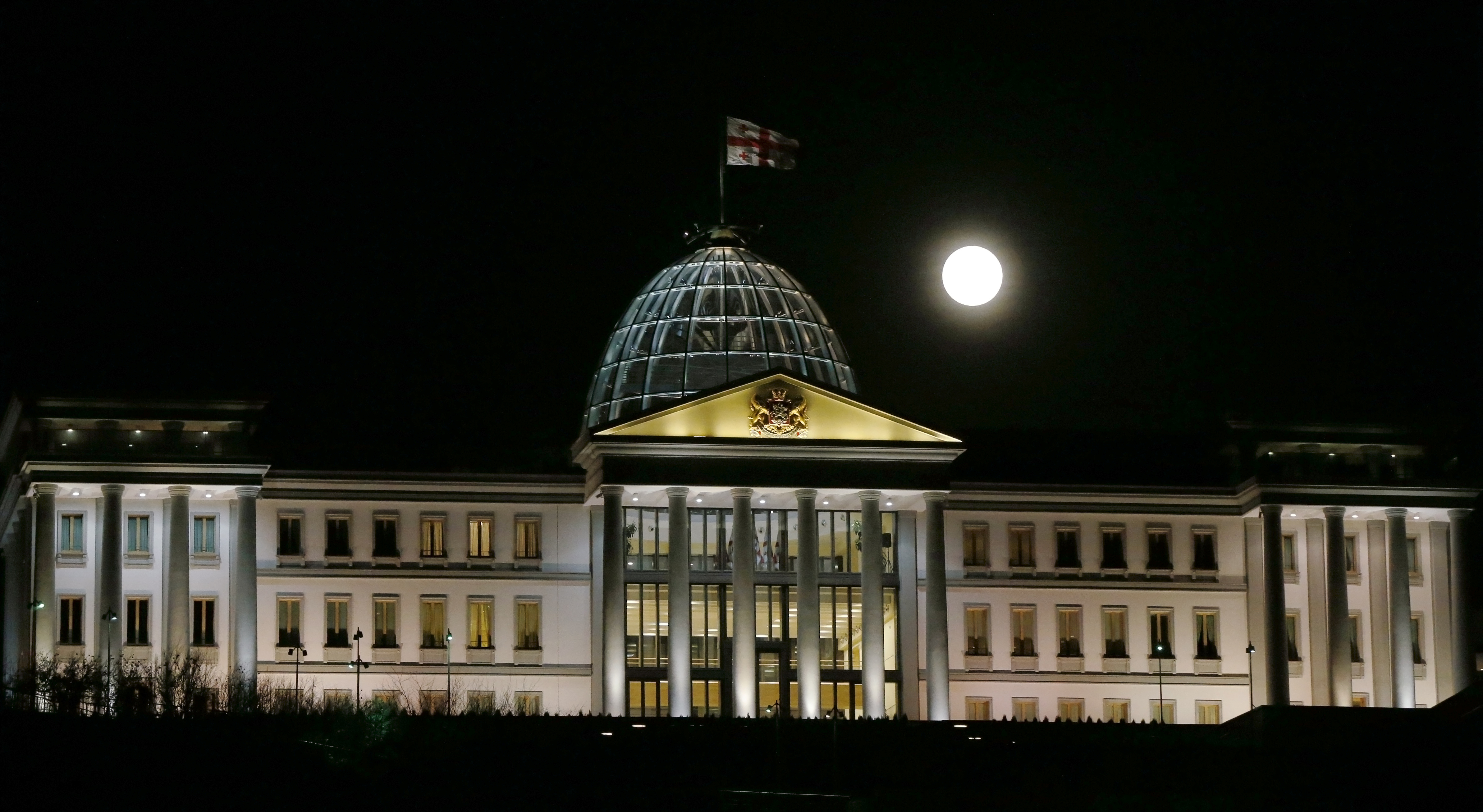 The glowing moon is seen above the presidential palace in Tbilisi, Georgia. Photo by David Mdzinarishvili/Reuters