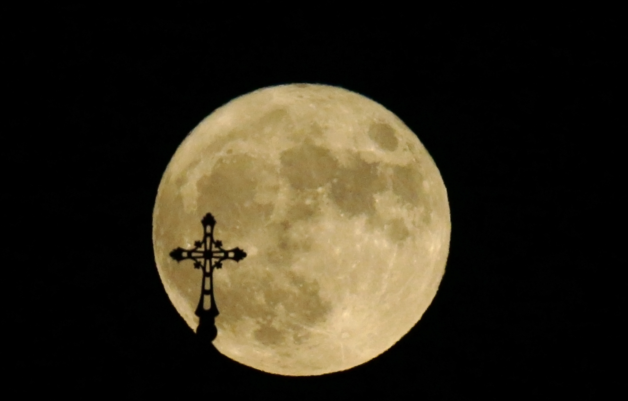 A cross atop a church in Tbilisi, Georgia is silhouetted against the supermoon. Photo by David Mdzinarishvili/Reuters