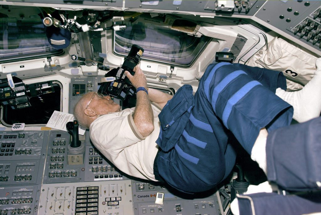 Astronaut and U.S. Senator John Glenn positions himself to take photos from the Discovery's aft flight deck windows on October 30, 1998. Photo courtesy NASA.