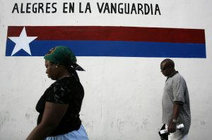 "People walk past a sign reading ""Happy in the vanguard"", on a street in Havana. Afro-Cubans are often subject to racial prejudice and disproportionate imprisonment for dissent. Photo by Claudia Daut/Reuters"