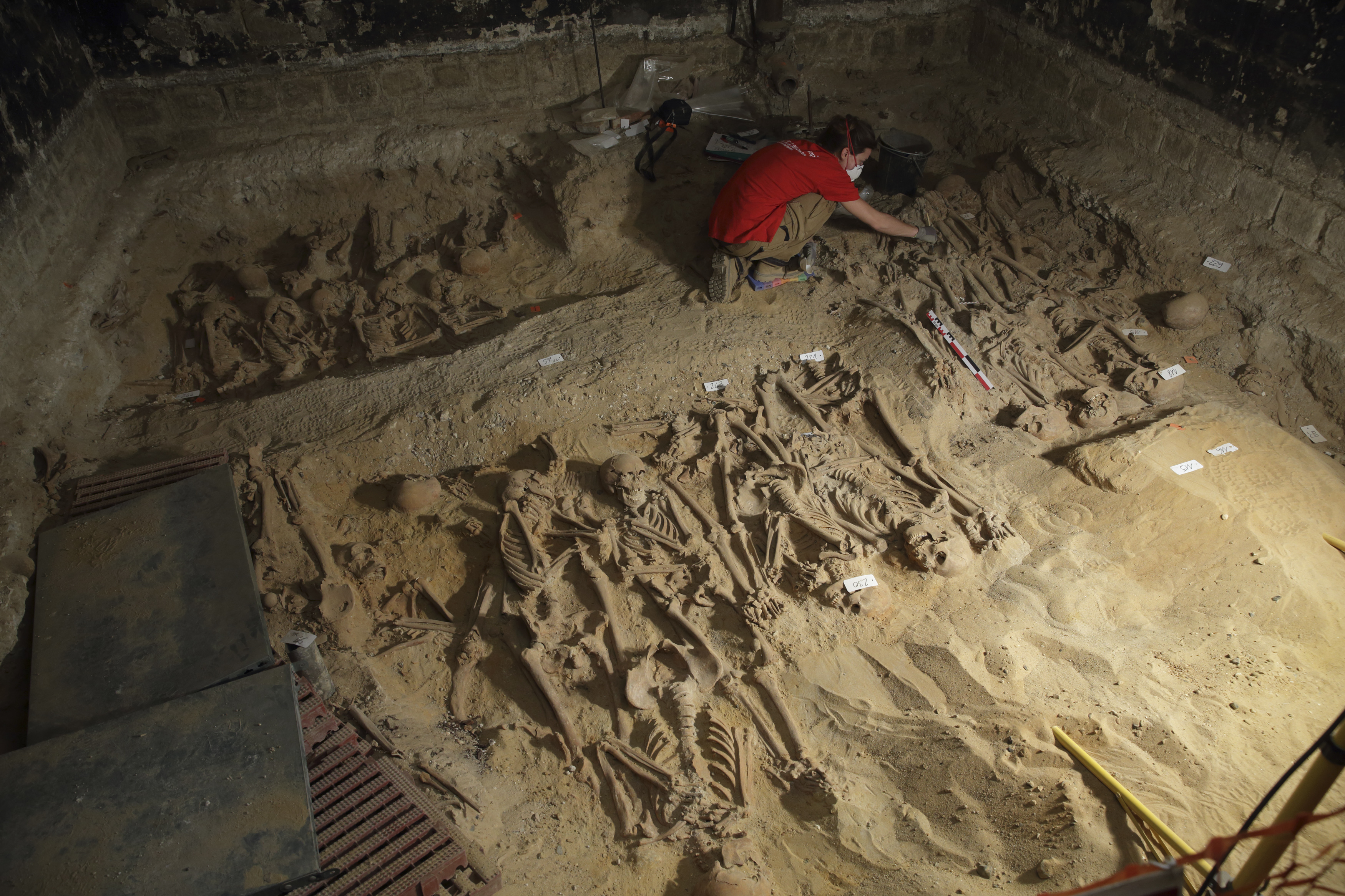 "An archaeologist works March 10, 2015 at the site where eight mass graves, with more than 200 skeletons, were found under the Monoprix Reaumur Sebastopol store in Paris. The discovery, made during renovation work in the cellar of the branch of Monoprix, has revealed what experts believe are victims of a sudden illness resembling an outbreak of Bubonic plague and could prove useful to historians studying burials in the Middle Ages. Eight communal graves have so far been discovered, seven small plots and one much larger one in which 150 skeletons have already been unearthed. The supermarket stands on the site of the cemetery of the Trinity hospital, founded in the 12th century and destroyed at the end of the 18th, and experts say the organisation of the graves points to a ""mass mortality crisis"". Picture taken March 10, 2015. Photo By Philippe Wojazer"