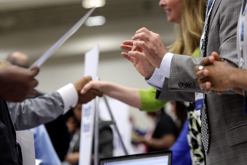 Corporate recruiters (R) gesture and shake hands as they talk with job seekers at a Hire Our Heroes job fair targeting unemployed military veterans and sponsored by the Cable Show, a cable television industry trade show in Washington, June 11, 2013. REUTERS/Jonathan Ernst/File Photo GLOBAL BUSINESS WEEK AHEAD PACKAGE SEARCH BUSINESS WEEK AHEAD 10 OCT FOR ALL IMAGES - RTSRJ2F