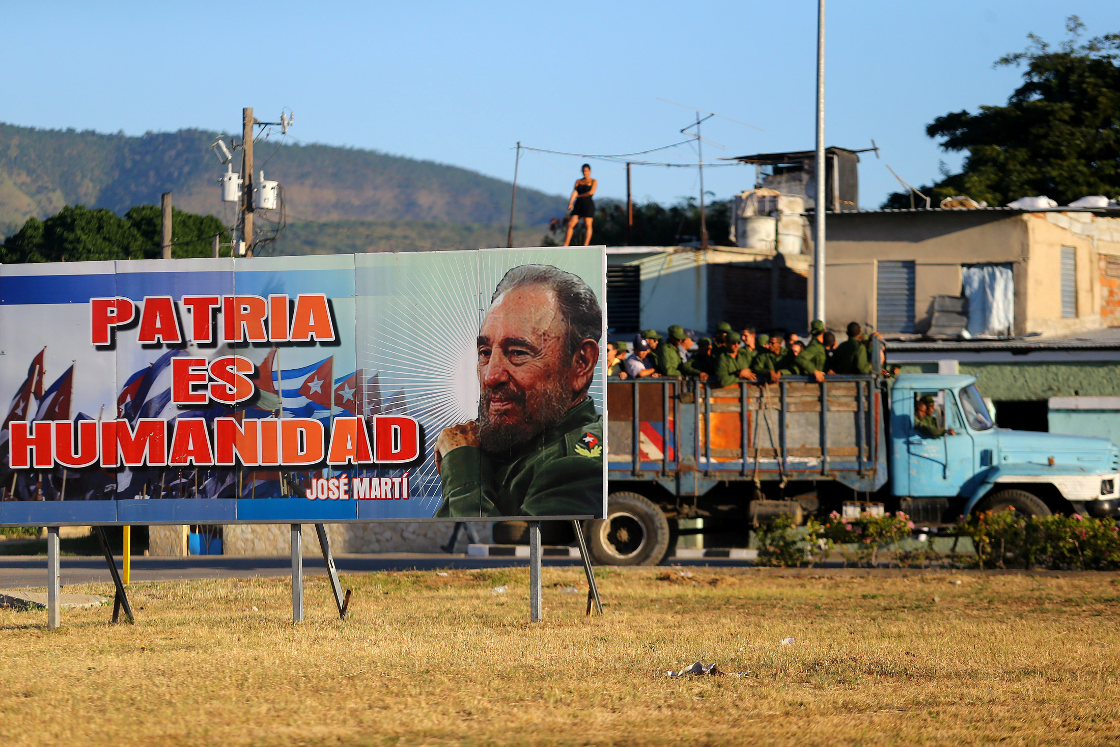 Soldiers stand in the back of a truck while driving past a billboard with a photograph of Cuba's former President Fidel Castro before Castro's ashes are to drive toward Santa Ifigenia cemetery in Santiago de Cuba, Cuba, December 4, 2016. Photo By Ivan Alvarado/Reuters